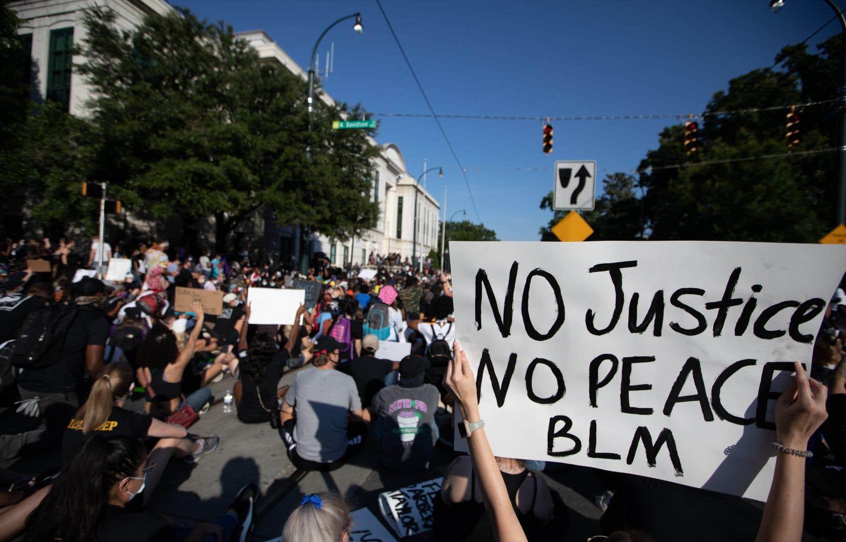 Des gens manifestent pour la fin des violences policières lors d'un rassemblement organisé dans le centre-ville de Charlotte, en Caroline du Nord.