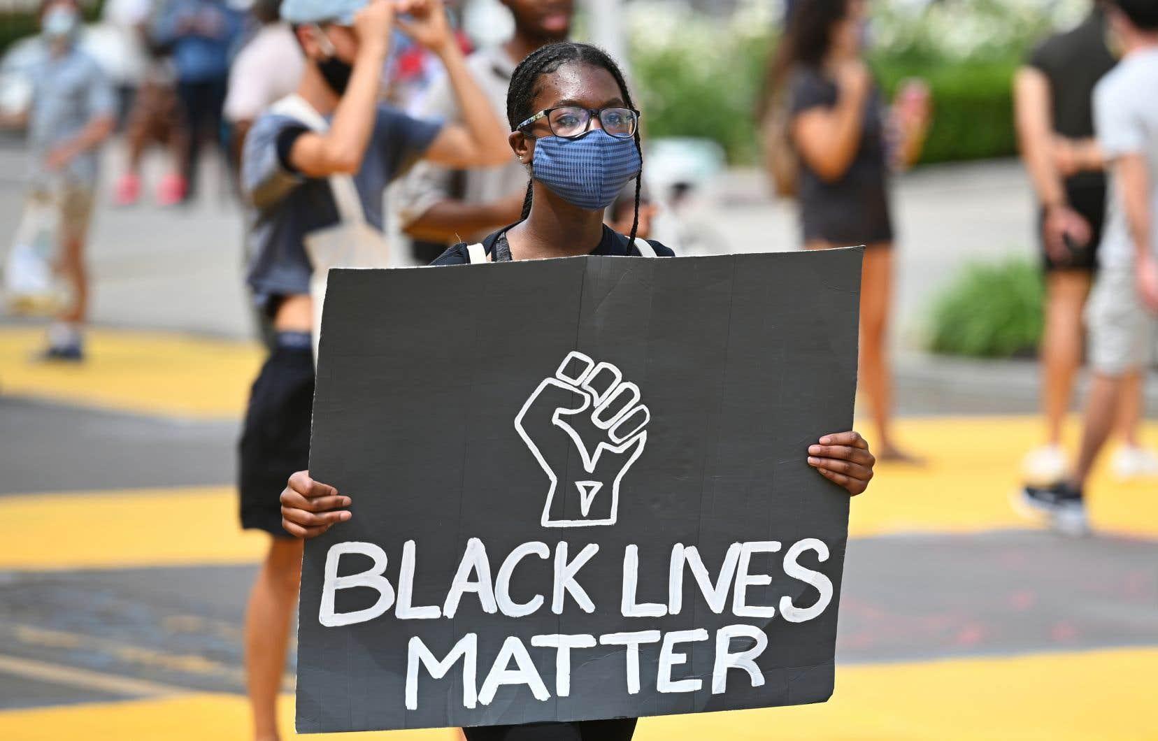 Une manifestante a brandi une affiche pour dénoncer les brutalités policières à l'encontre de la minorité noire.