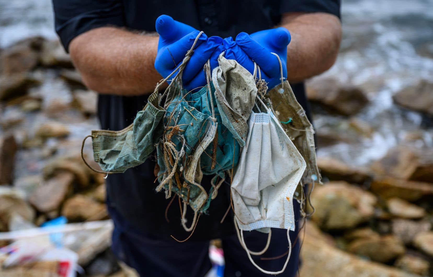 Si les mesures de confinement à l'échelle de la planète ont réduit les émissions de gaz à effet de serre, la pandémie a aussi induit des réflexes polluants. Ici, des masques jetables échoués une plage à HongKong.