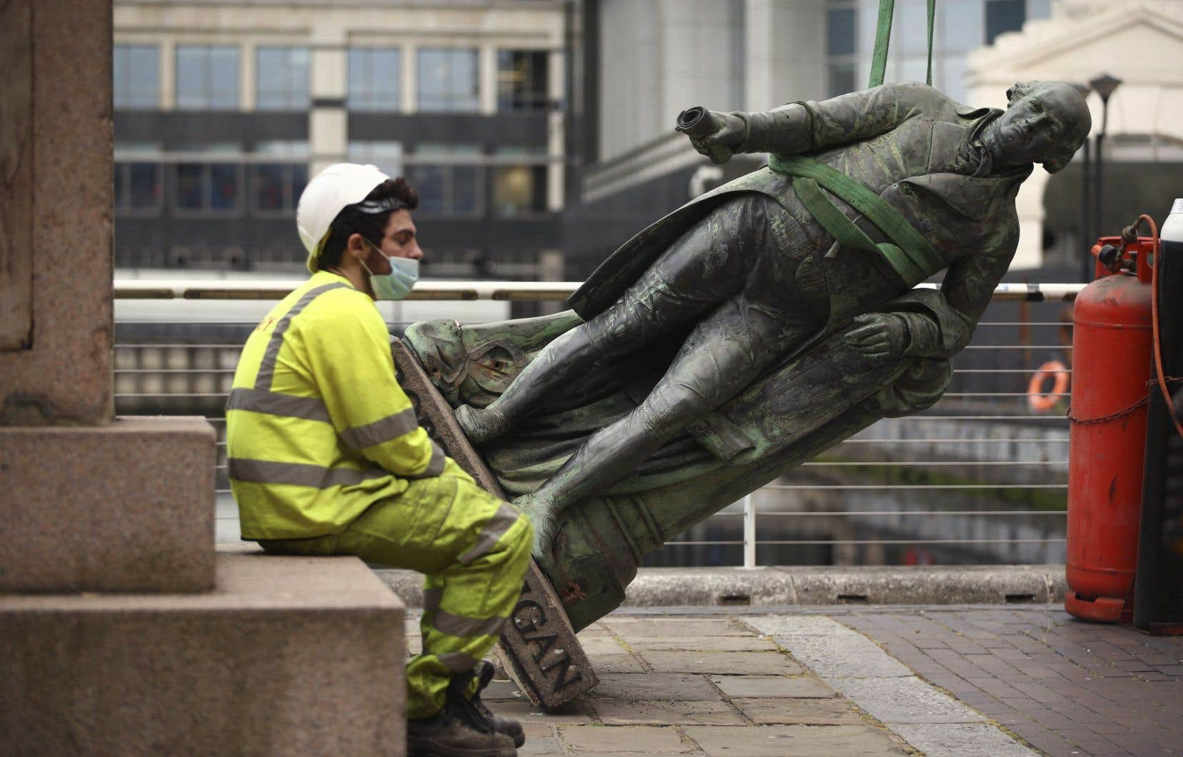 Un travailleur se repose après que la statue du propriétaire d'esclaves Robert Milligan a été démontée, à West India Quay, à l'est de Londres, le mardi 9 juin 2020, après qu'une manifestation a vu des militants anti-racisme abattre une statue d'un marchand d'esclaves à Bristol.