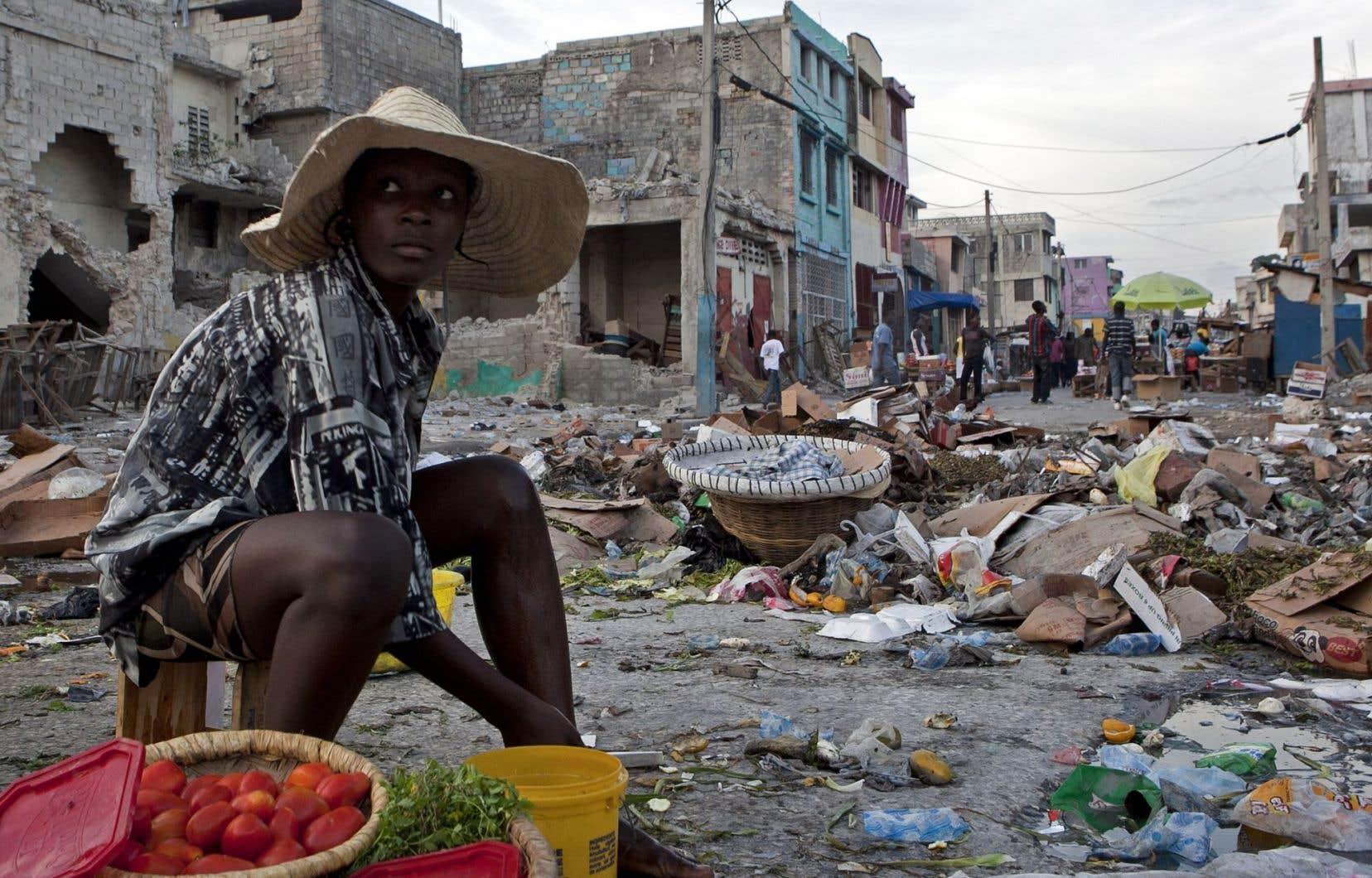 Une jeune commerçante offre ses produits au milieu des débris qui encombrent toujours le centre-ville de Port-au-Prince un an après le séisme.