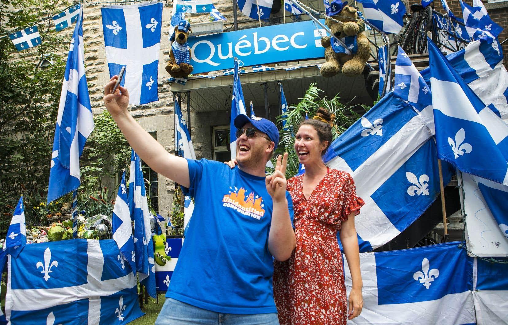 Billi Deraspe et Joannie Desrosiers se sont prêté à une séance photo devant un bloc appartement du quartier Hochelaga-Maisonneuve entièrement décoré aux couleurs de la Fête nationale.