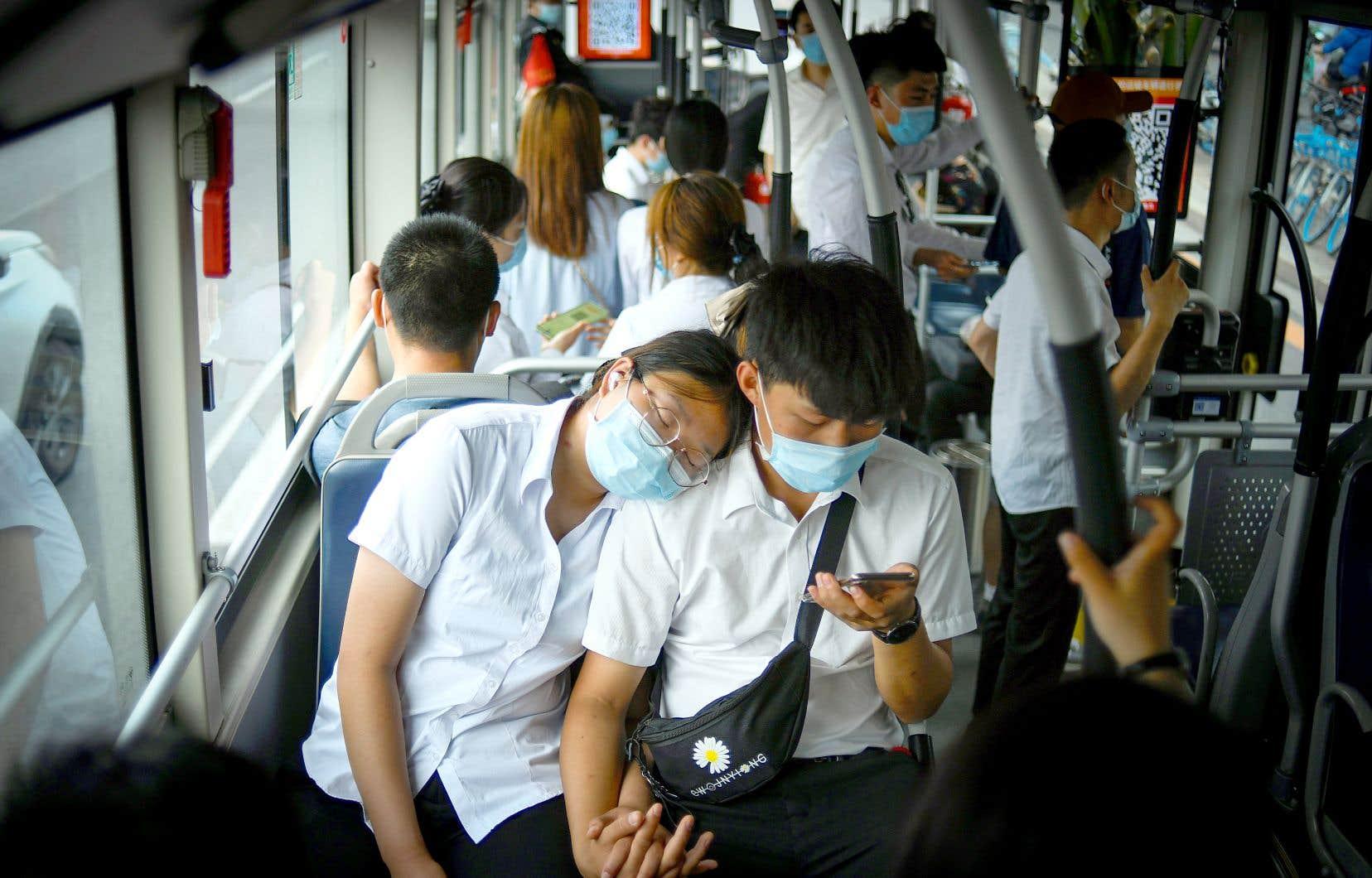 Un couple masqué est photographié pendant son trajet en autobus à Pékin, en Chine. La région de la capitale traverse présentement une hausse de la contagion.