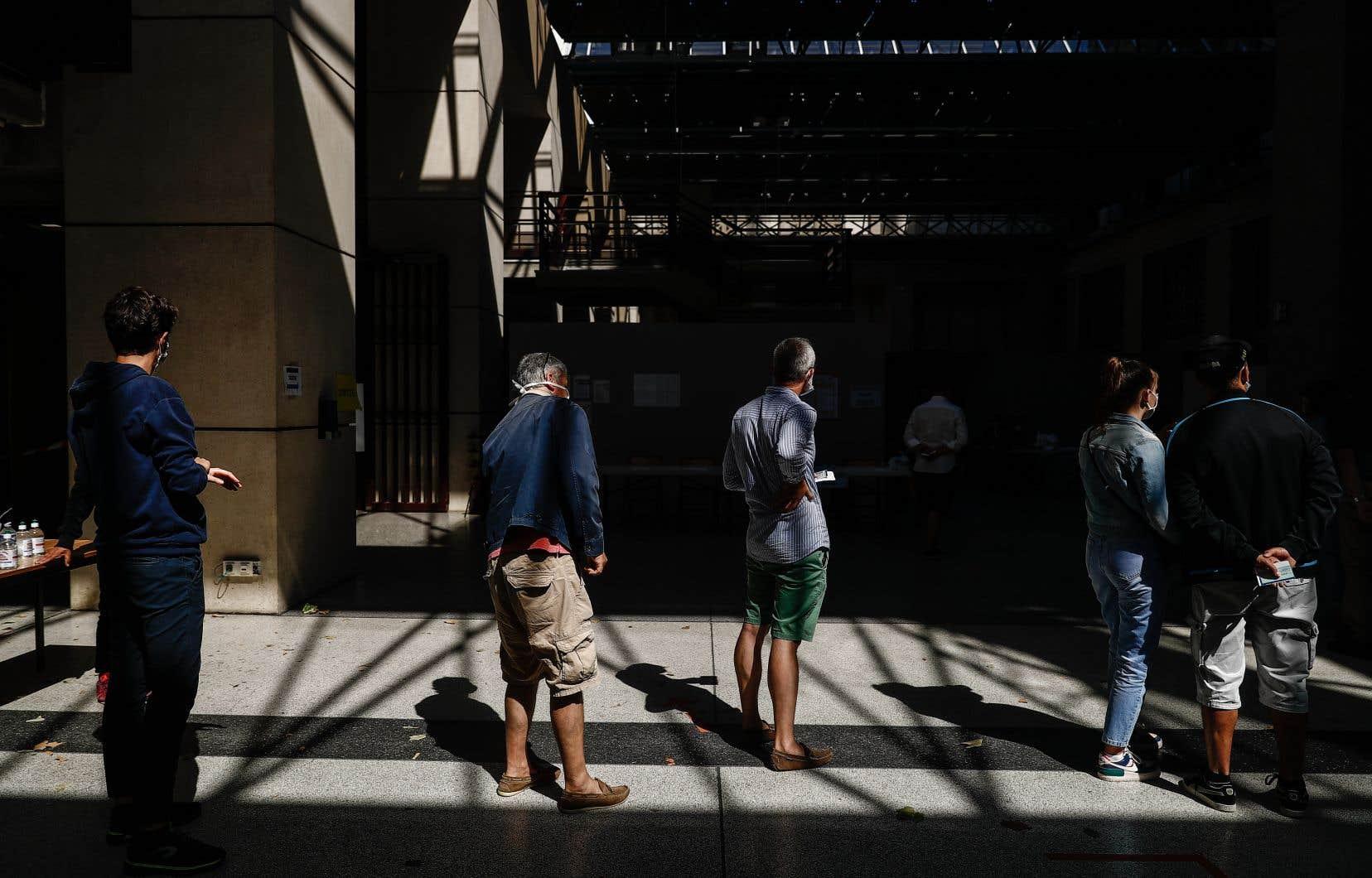 Des électeurs français font la file pour voter à Le Havre, dimanche au second tour des élections municipales.