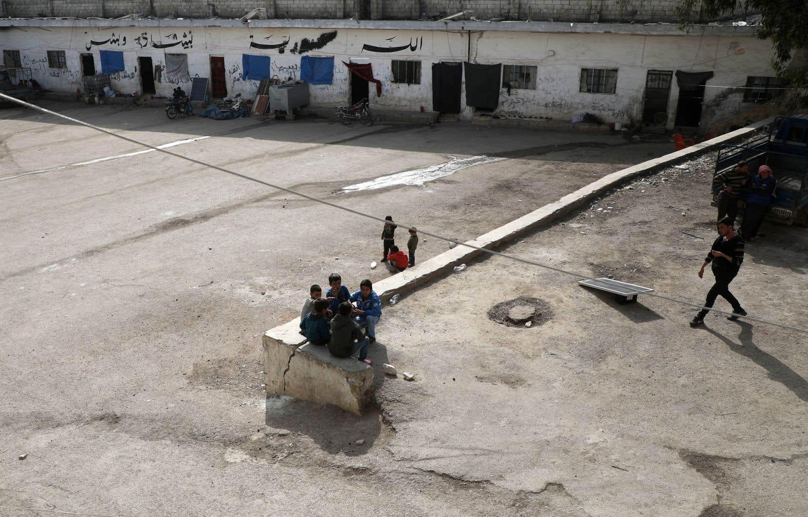 Human Rights Watch appelle Ottawa à commencer immédiatement à ramener les détenus au pays — à commencer par les 26 enfants canadiens qui se trouvent dans ces camps. Sur la photo, des enfants syriens déplacés par la guerre jouent dans une ancienne prison reconvertie en abri de fortune.