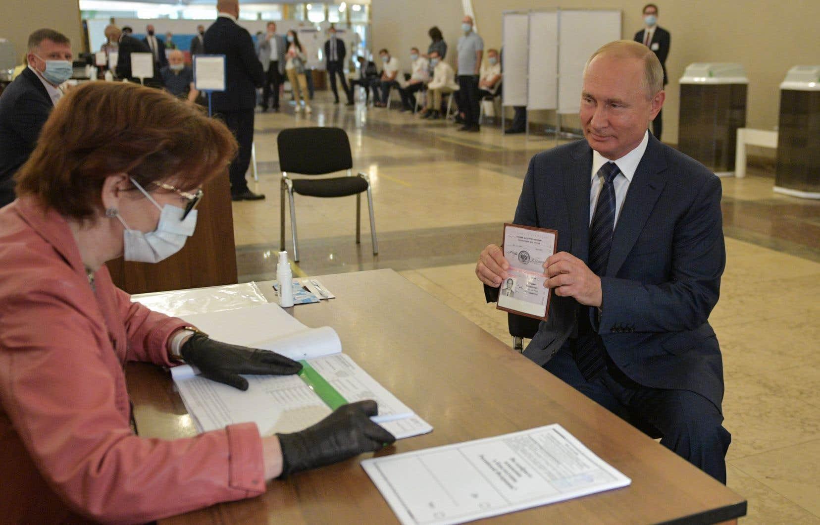 Le président Poutine a, lui, voté à Moscou mercredi sans moyens de protection, contrairement à l'assesseur à laquelle il faisait face.
