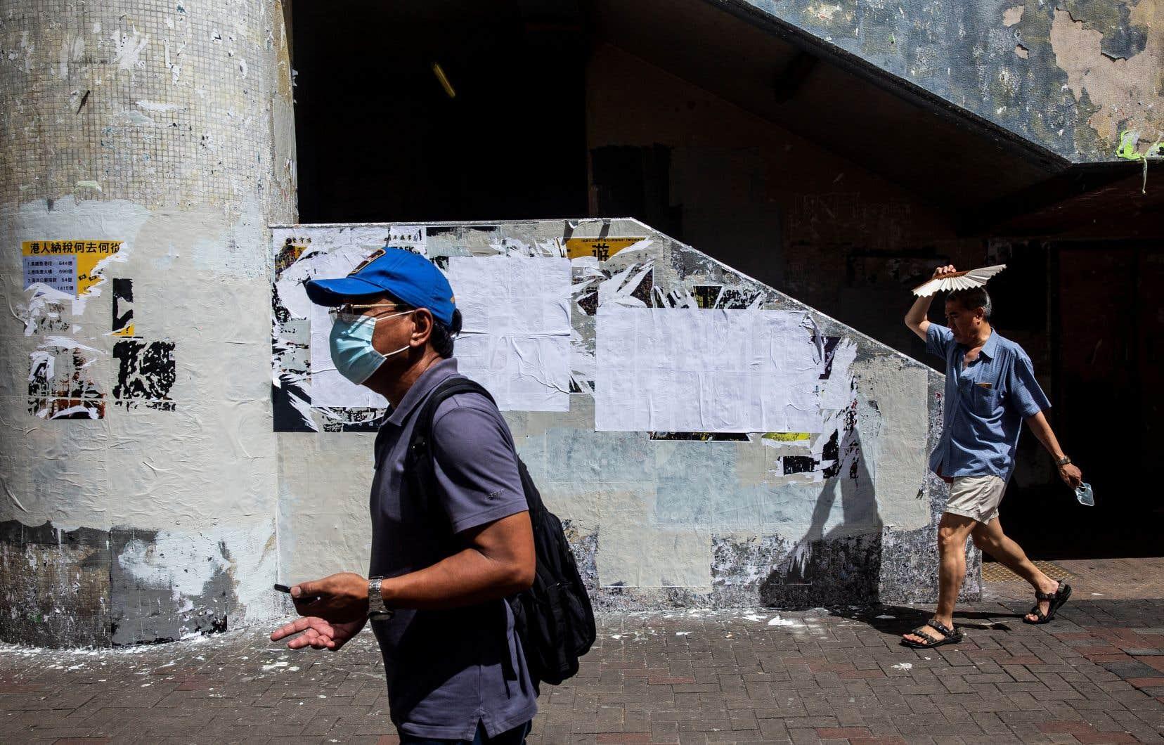 Des citoyens de Hong Kong passent devant un mur avec des affiches pro-démocratie qui ont été recouvertes de papier vierge.