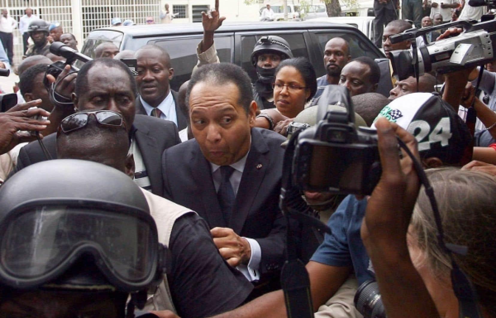 Jean-Claude Duvalier entour&eacute; de policiers, de gardes du corps et journalistes lors de son arriv&eacute;e au parquet de Port-au-Prince, hier. Son cas est maintenant entre les mains d&rsquo;un juge d&rsquo;instruction. En attendant, l&rsquo;ancien dictateur est libre.<br />