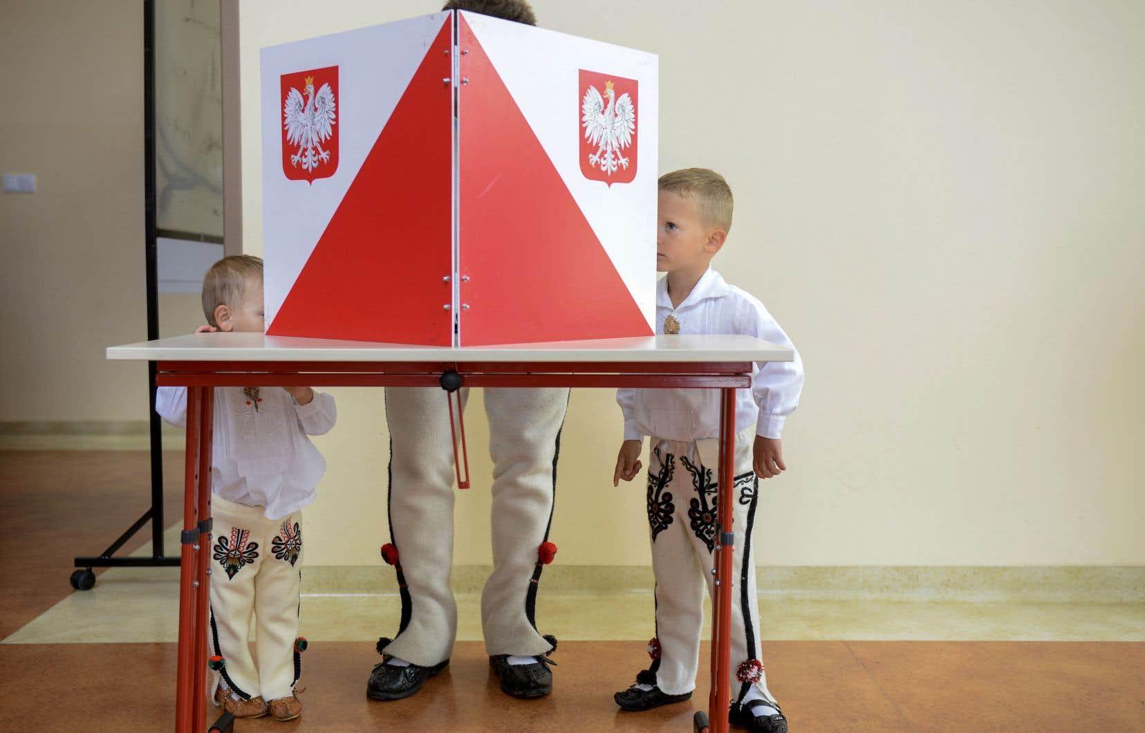 Un homme et ses deux fils se sont rendus au bureau de vote vêtus d'un habit traditionnel polonais. Virus oblige, les électeurs se présentaient masqués dimanche et, après s'être passé les mains au gel désinfectant, utilisaient leur propre stylo pour voter.