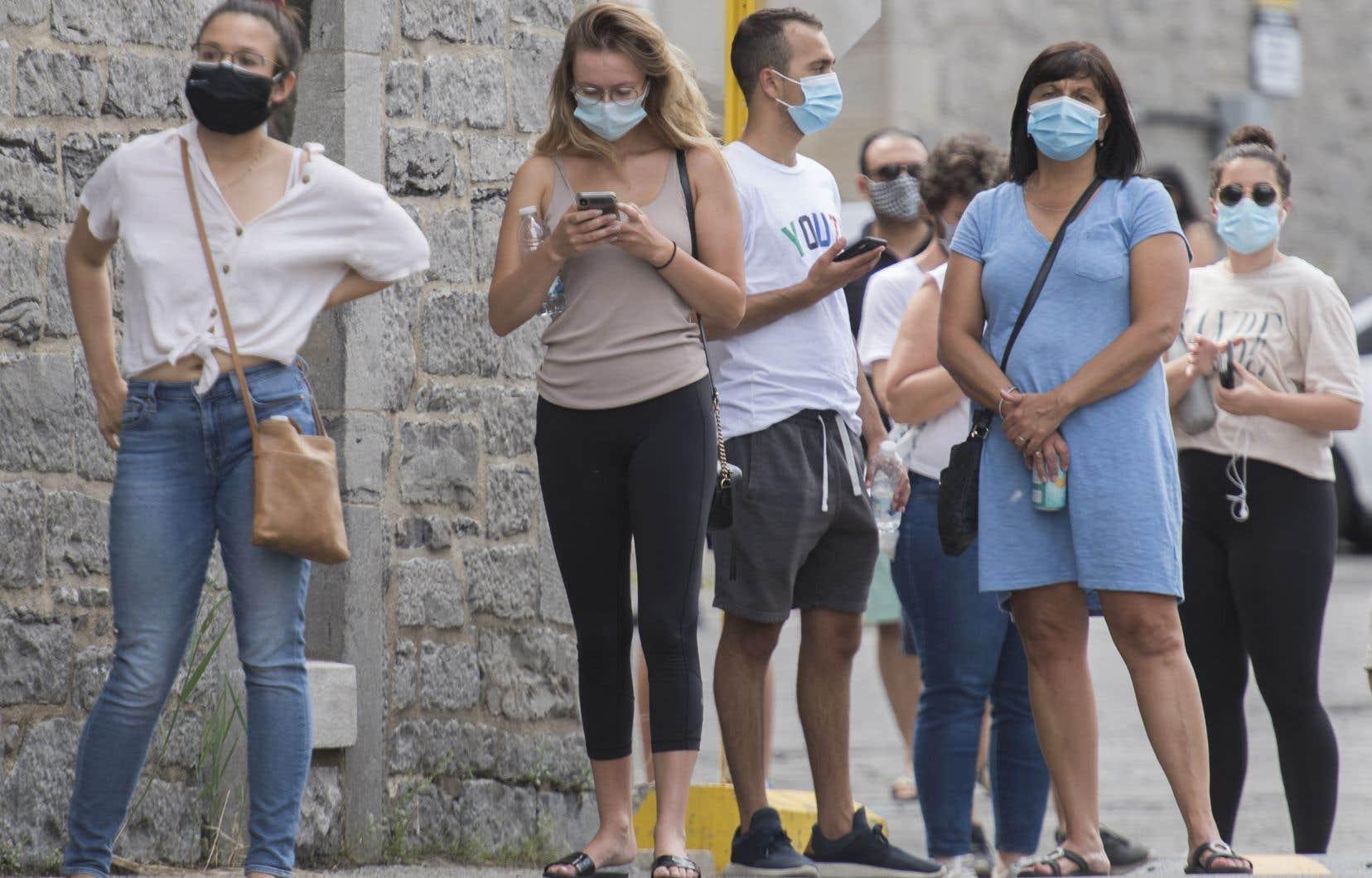 Des citoyens font la file pour se faire tester à la COVID-19 à Montréal, dimanche.