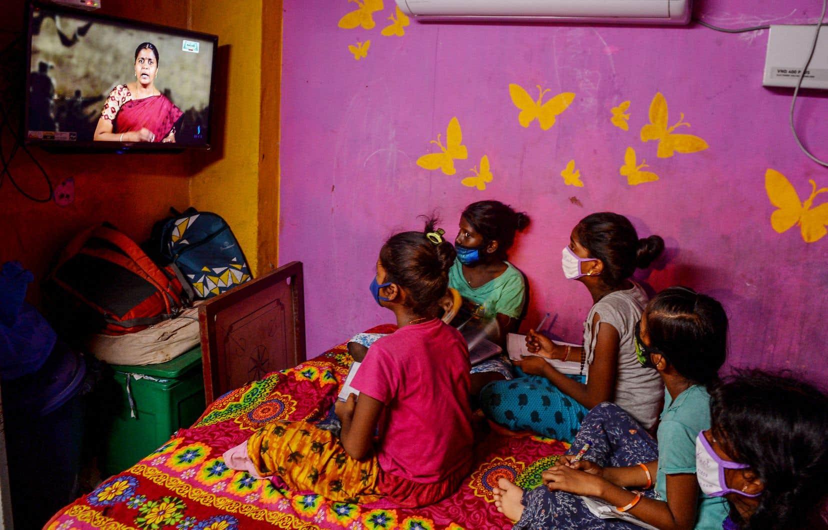 De jeunes Indiens suivent un cours à distance devant la télévision. Le gouvernement du pays a mis en place durant le confinement un programme d'éducation diffusé à la télévision pour les enfants de la deuxième à la dixième année.