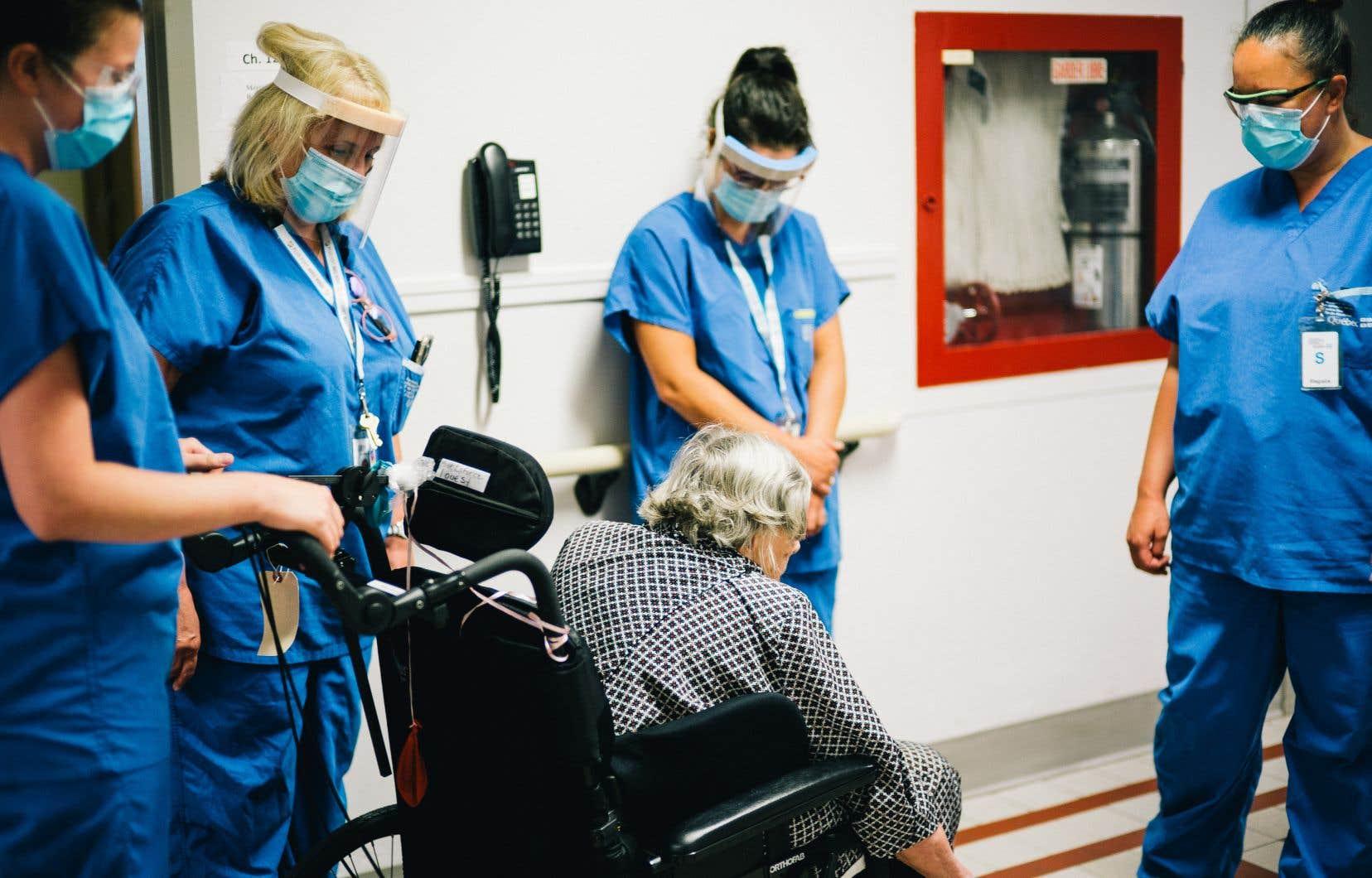 Elizabeth Carignan aide une résidente à se déplacer en chaise roulante. La stagiaire fait ses premiers pas à titre de préposée aux bénéficiaires à l'Institut universitaire de gériatrie de Montréal.