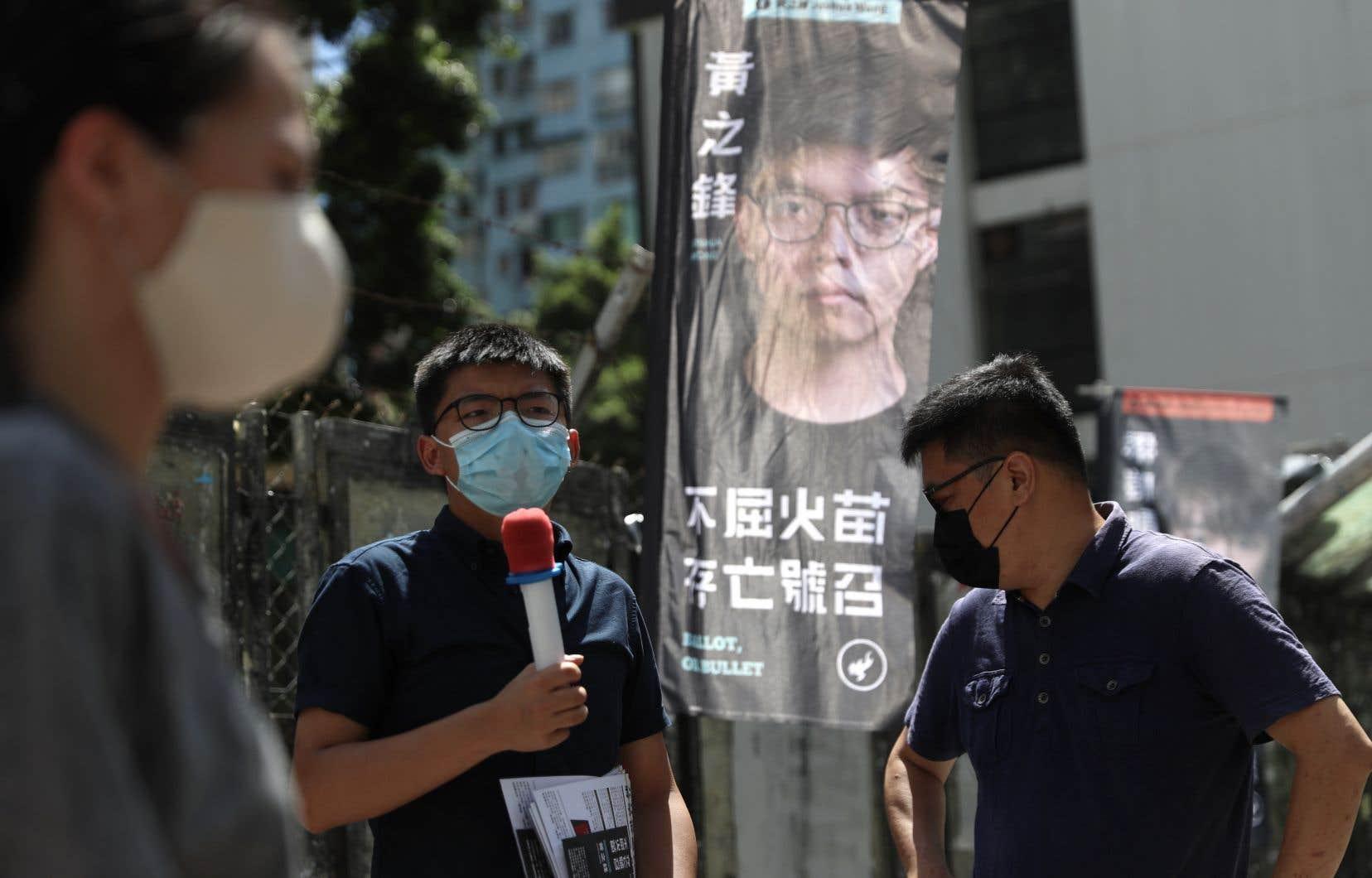 Le militant prodémocratie Joshua Wong (sur l'affiche),qui a été en 2014 le visage du «Mouvement des Parapluies», fait partie des douze candidats dont la candidature aux législatives de Hong Kong a été invalidée.