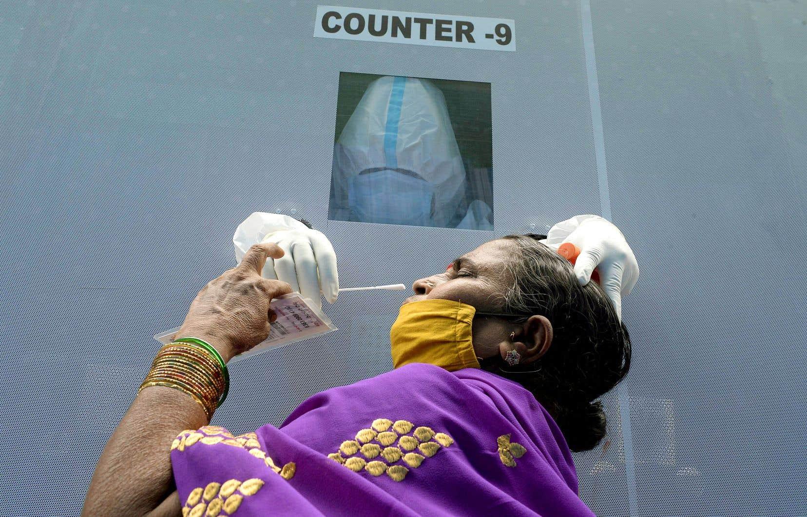 Un travailleur de la santé portant un équipement de protection personnelle effectue des tests dans une unité mobile de détection du coronavirus à Hyderabad, en Inde.