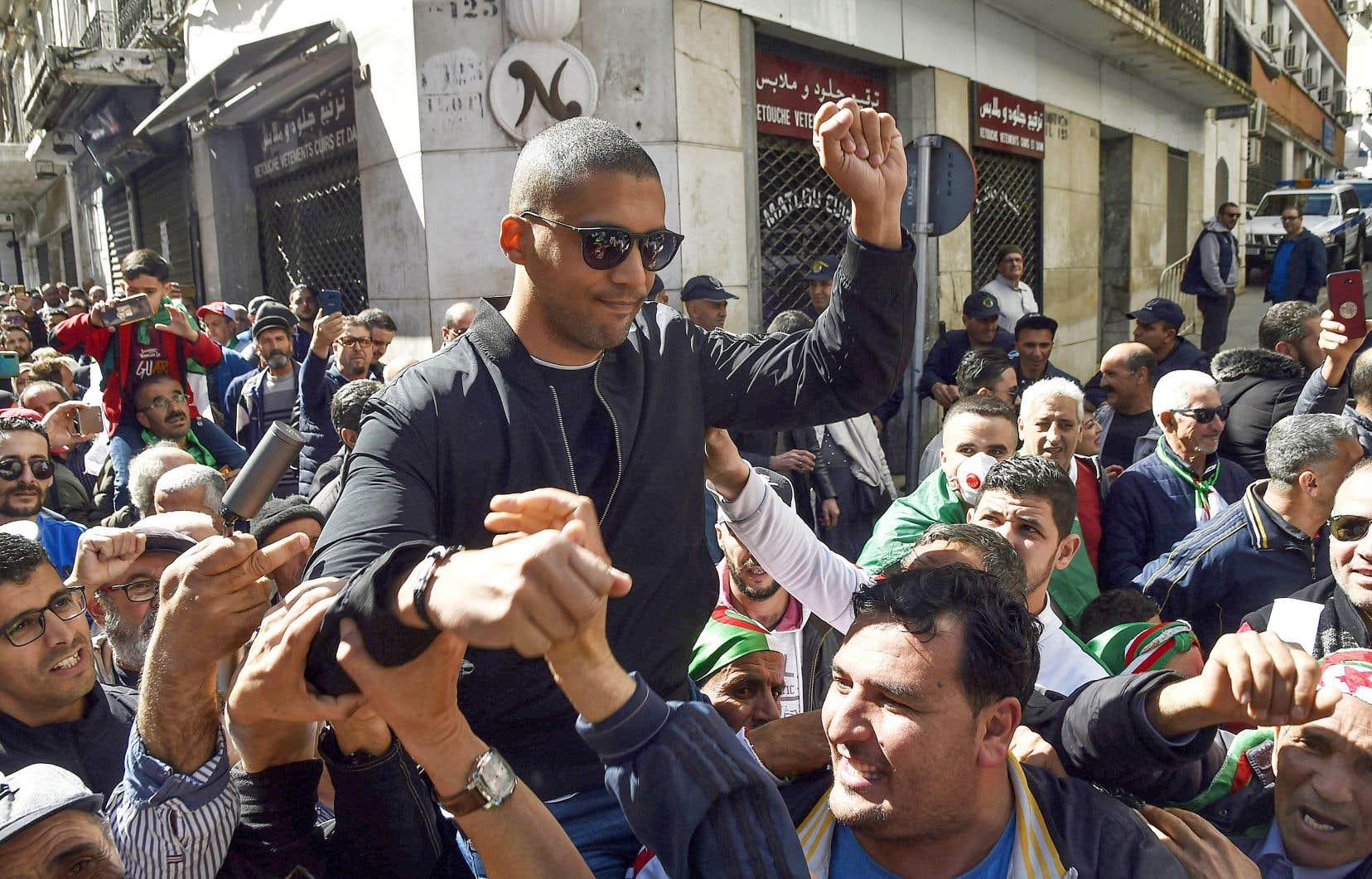 Des manifestants transportaient le journaliste Khaled Drareni après qu'il eut été brièvement détenu par les forces de sécurité à Alger, en mars dernier.