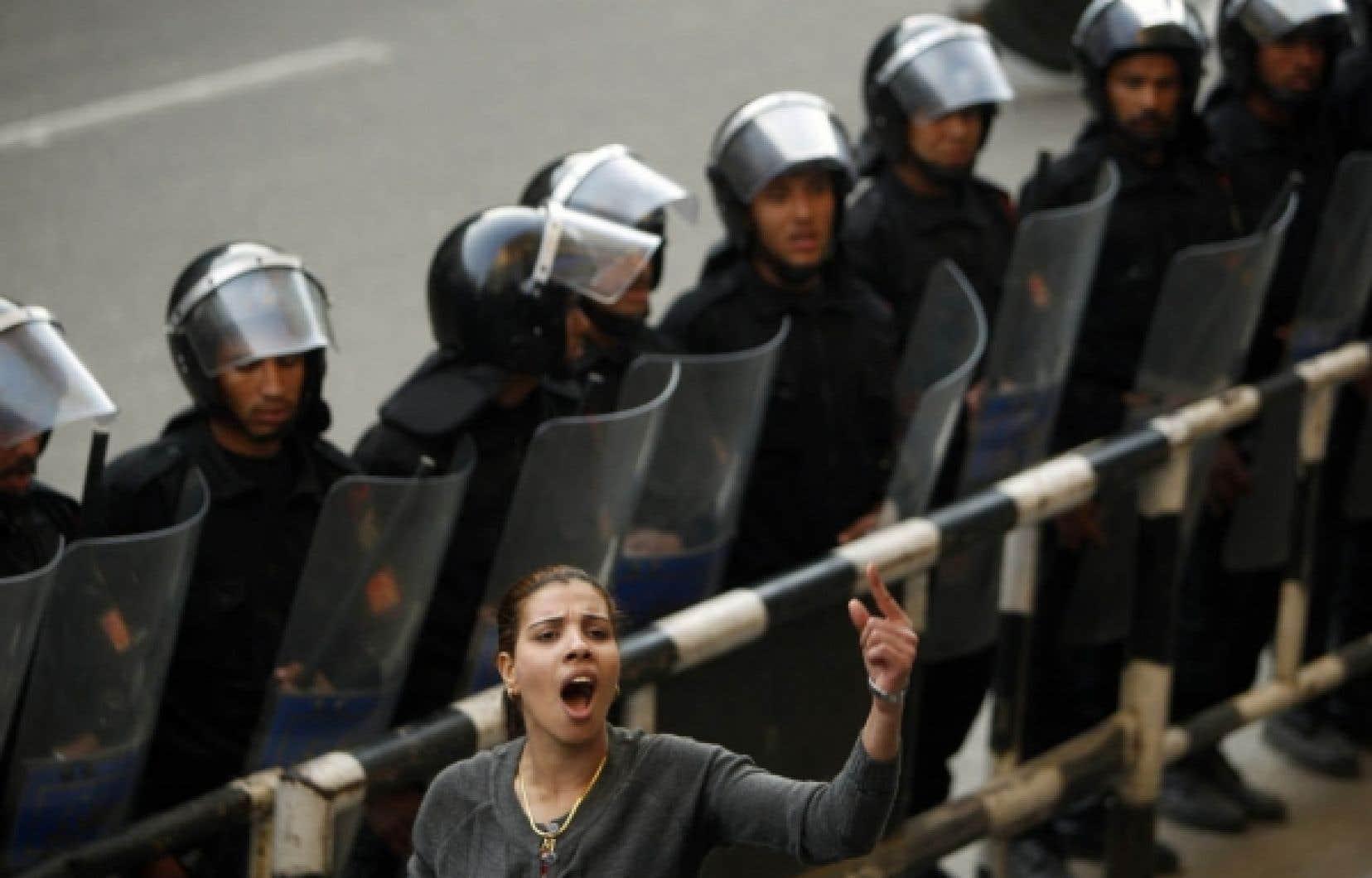 Une activiste &eacute;gyptienne scande des slogans contre le gouvernement du pr&eacute;sident Hosni Moubarak, en poste depuis 1981. Elle prenait part hier &agrave; une manifestation au centre-ville du Caire, surveill&eacute;e de pr&egrave;s par les policiers. Le soul&egrave;vement populaire qui a lieu en &Eacute;gypte depuis mardi se poursuit aujourd&rsquo;hui avec de grandes manifestations pr&eacute;vues un peu partout au pays et annonc&eacute;es sur les r&eacute;seaux sociaux.<br />