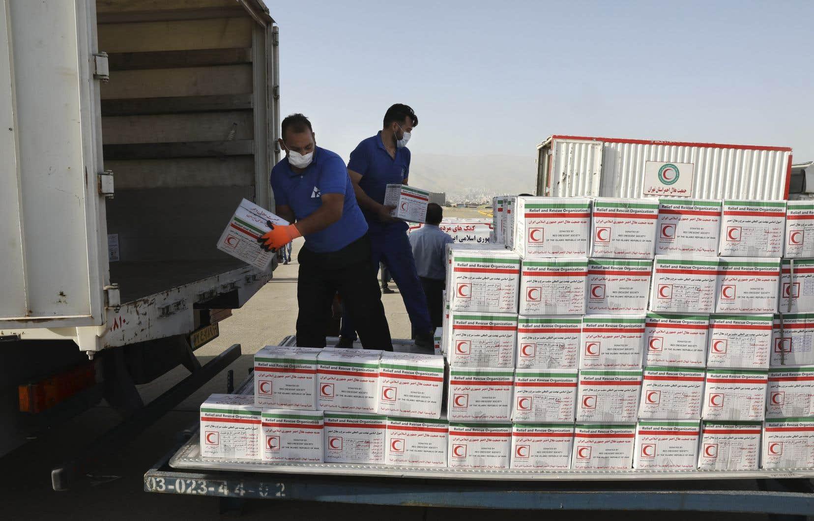 Des travailleurs iraniens déchargent des marchandises d'aide sanitaire destinées à être chargées dans un avion à destination de Beyrouth.