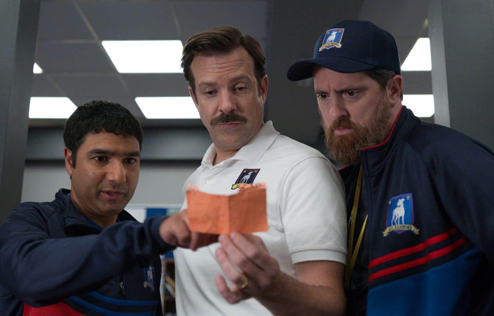 Le coach  Ted Lasso  (Jason  Sudeikis)  planifie une  stratégie pour ses joueurs  entouré de ses fidèles acolytes incarnés par Nick Mohammed (à gauche)  et Brendan Hunt  (à droite).