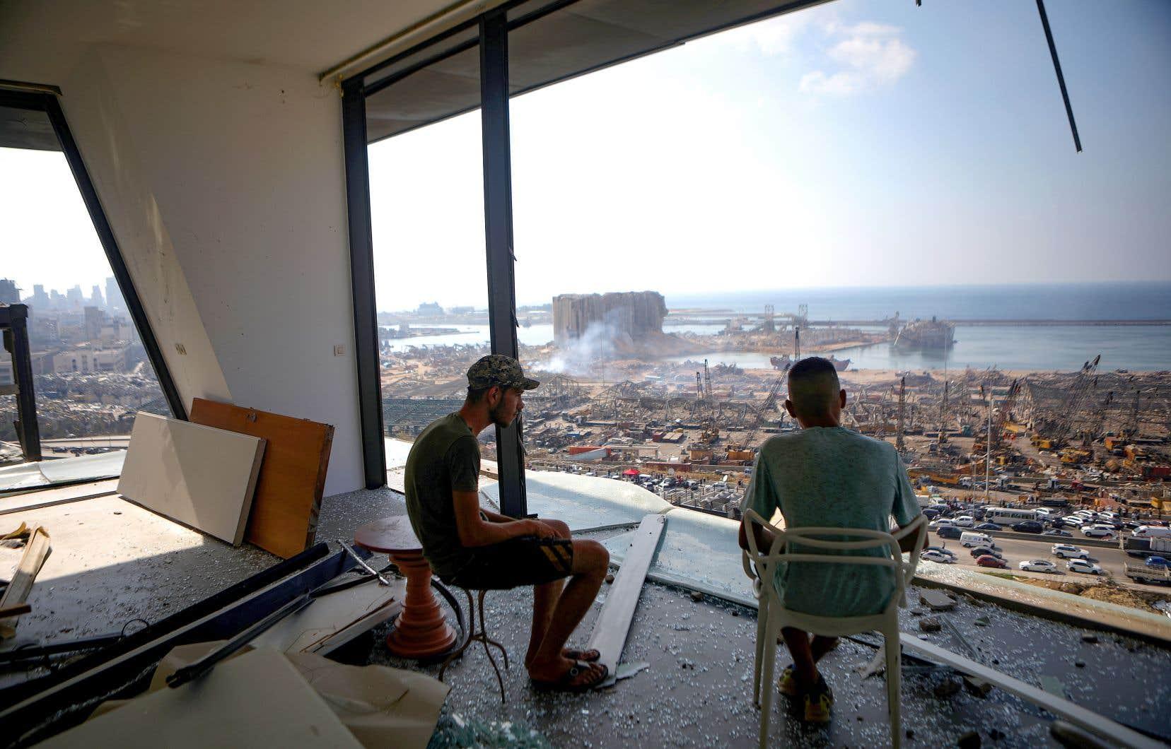 Deux hommes observent Beyrouth dévastée par les explosions depuis un appartement.