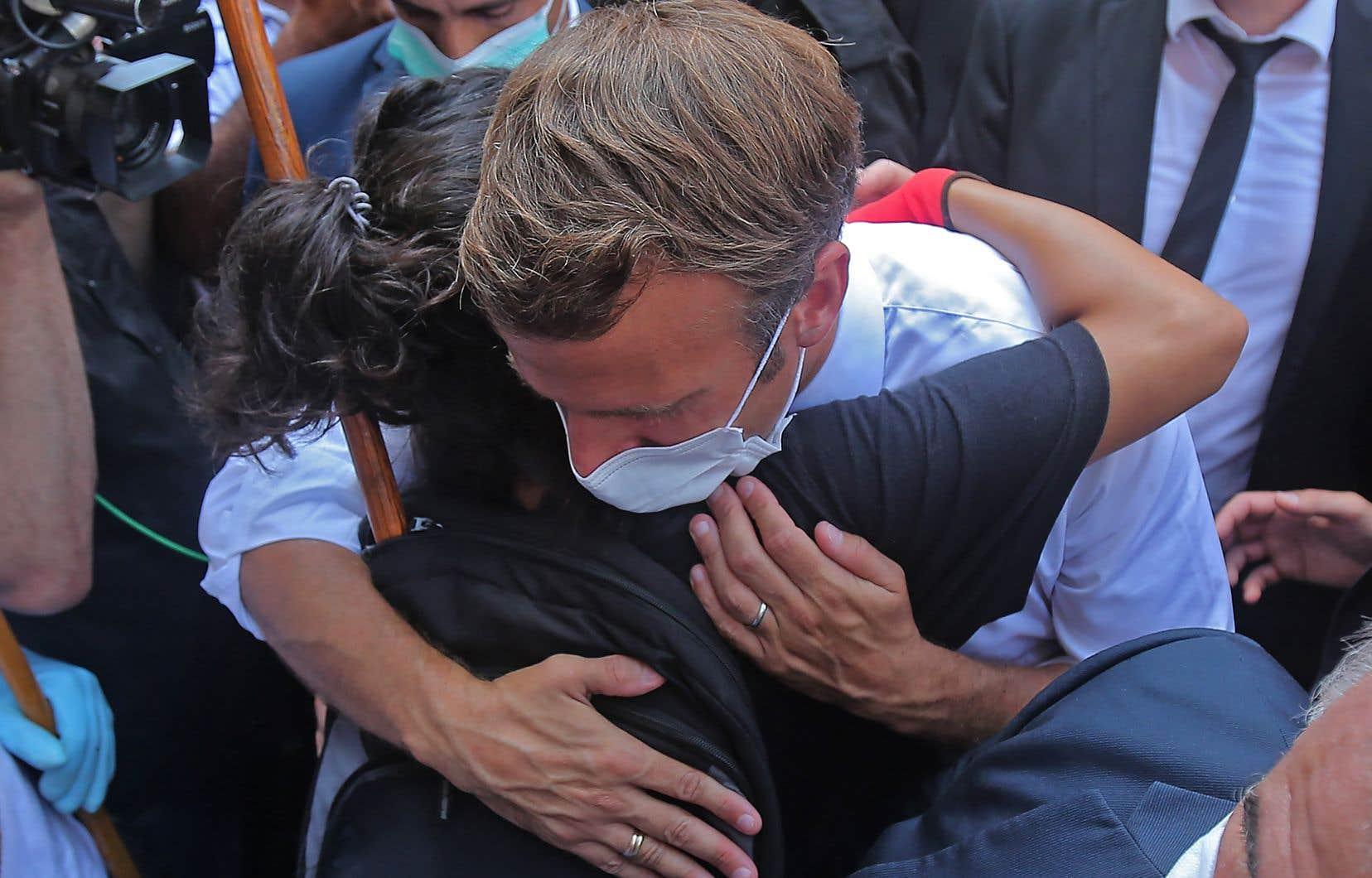 Une jeune libanaise enlace le président français Emmanuel Macron lors d'une visite dans le quartier de Gemmayzeh, qui a subi d'importants dégâts en raison d'une explosion massive dans la capitale libanaise.