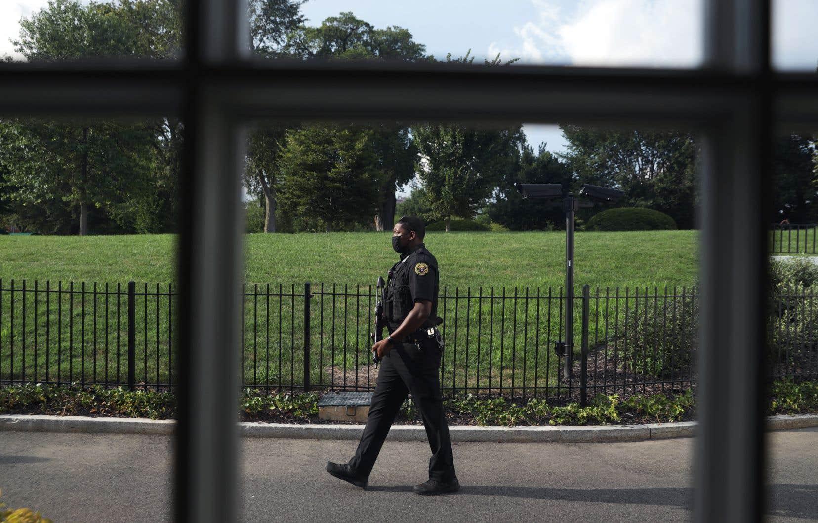 Un officier des services secrets américains montre la garde à l'extérieur de la salle de conférence de presse James Brady après que des tirs ont été signalés près de la Maison Blanche le 10 août 2020.
