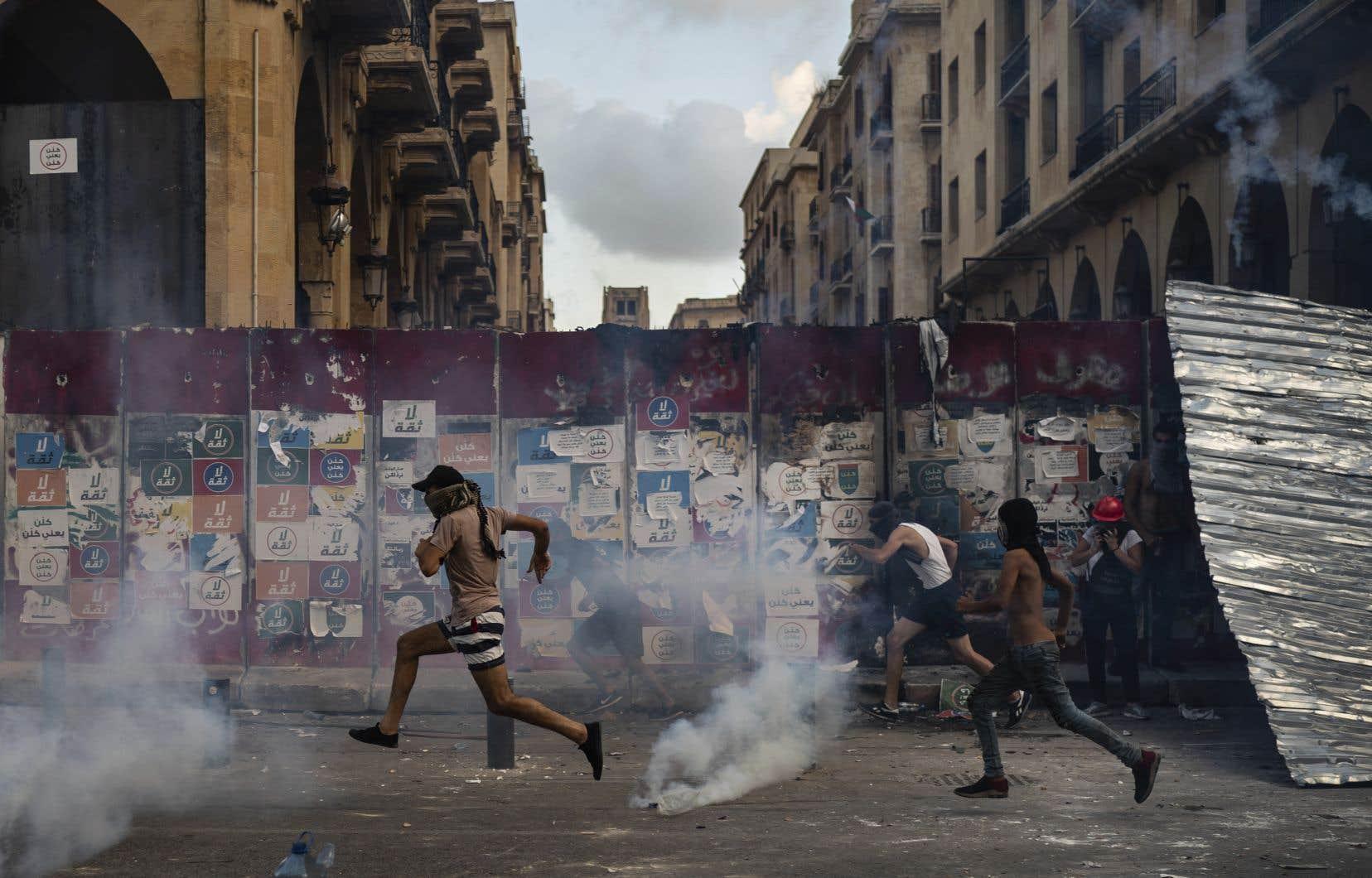 Des manifestants tentent d'échapper aux gaz lacrymogènes lancés par les forces de l'ordre à Beyrouth lundi.