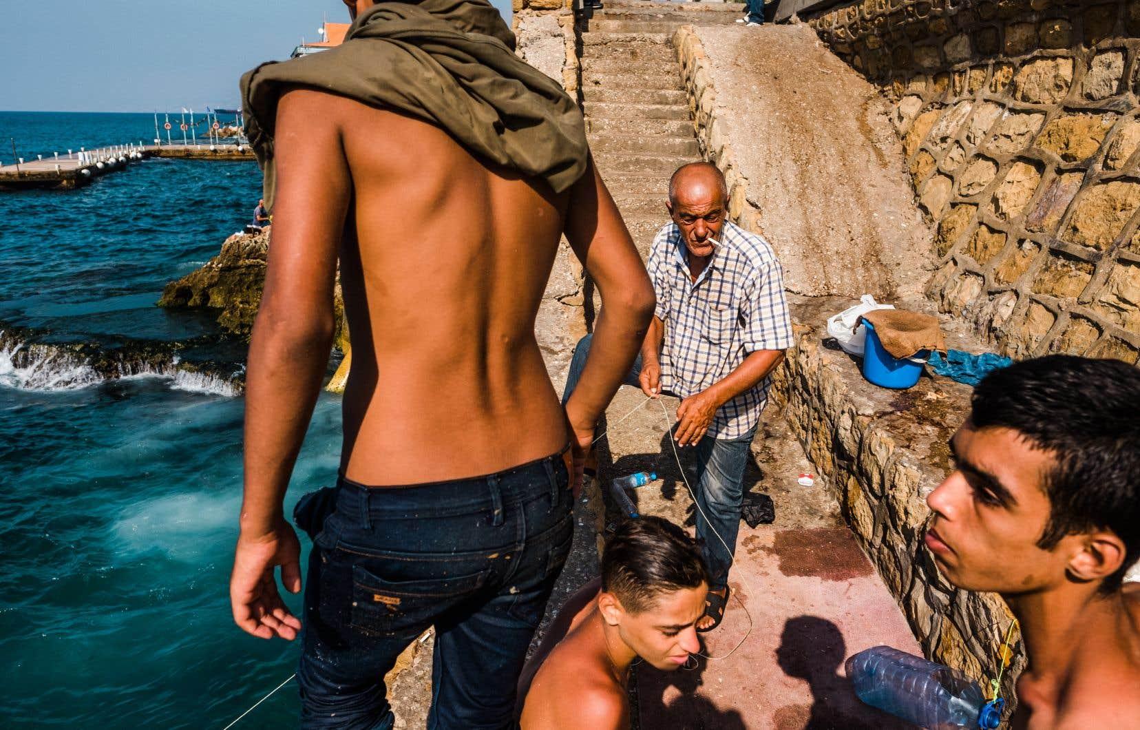 Mahmoud Awad (portant une chemise à carreaux) pêche des sardines sur la Corniche de Beyrouth, entouré de jeunes qui profitent du soleil.