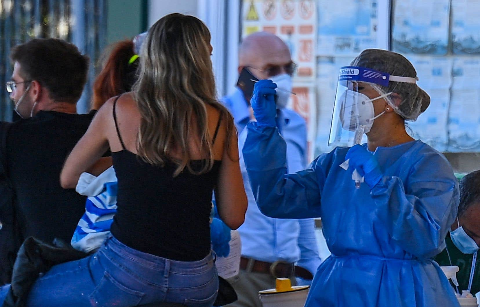 En Italie, des vacanciers débarquant du traversier en provenance de Sardaigne se soumettent à un test de dépistage pour la COVID-19.