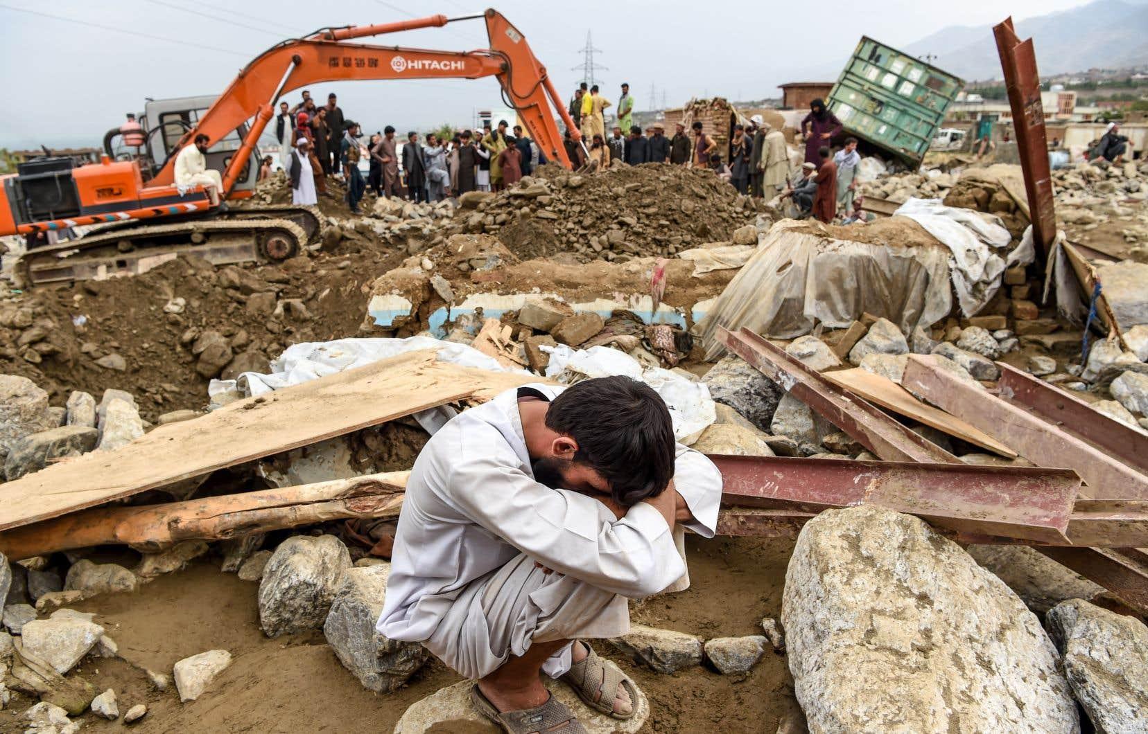 Les sauveteurs, aidés par des engins de terrassement, continuaient à fouiller les décombres, sous l'œil de dizaines d'habitants pataugeant dans la boue.