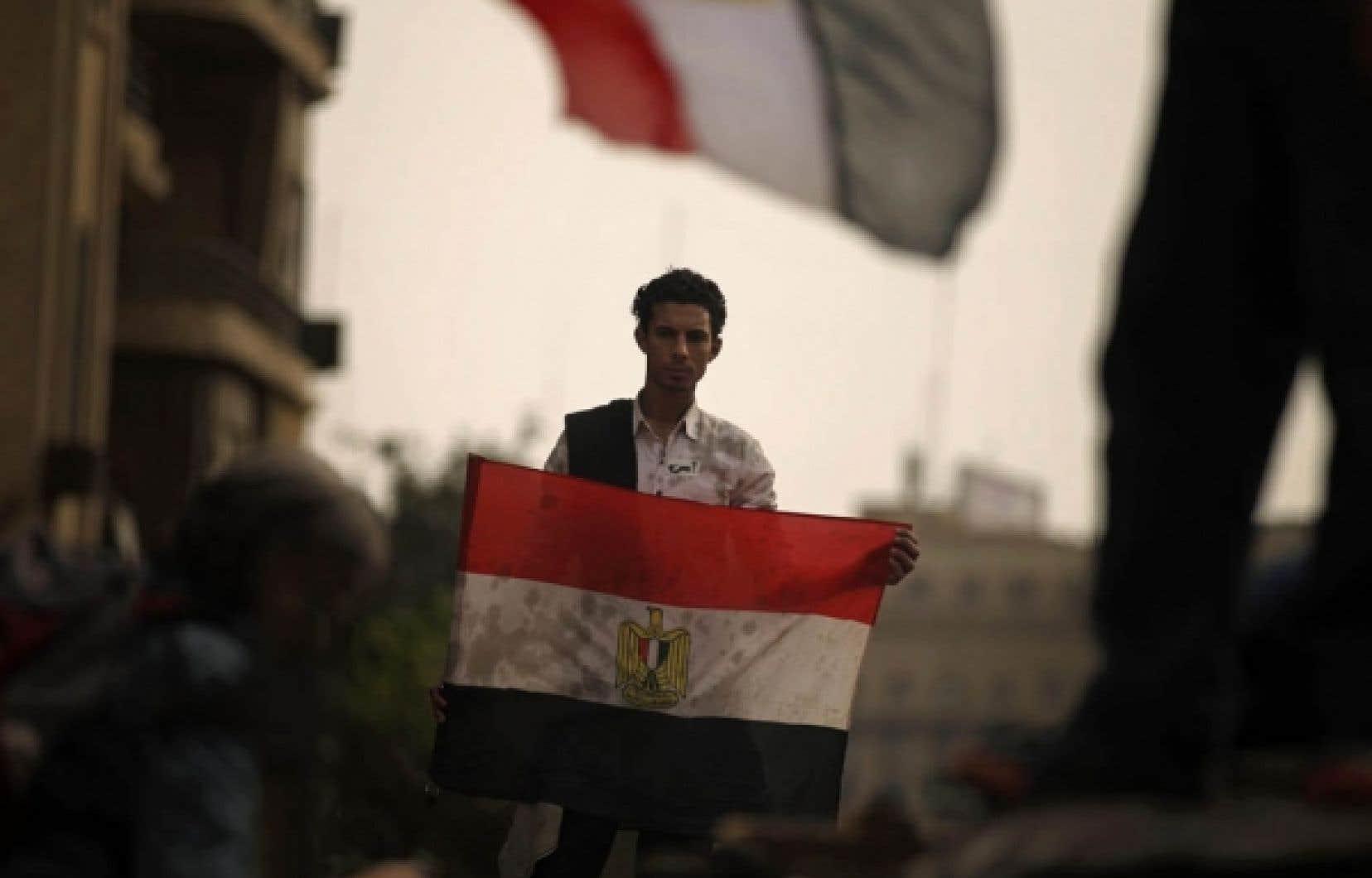 Un manifestant anti-Moubarak dans les rues du Caire, où plusieurs centaines de milliers de personnes se sont massées hier dans le calme.