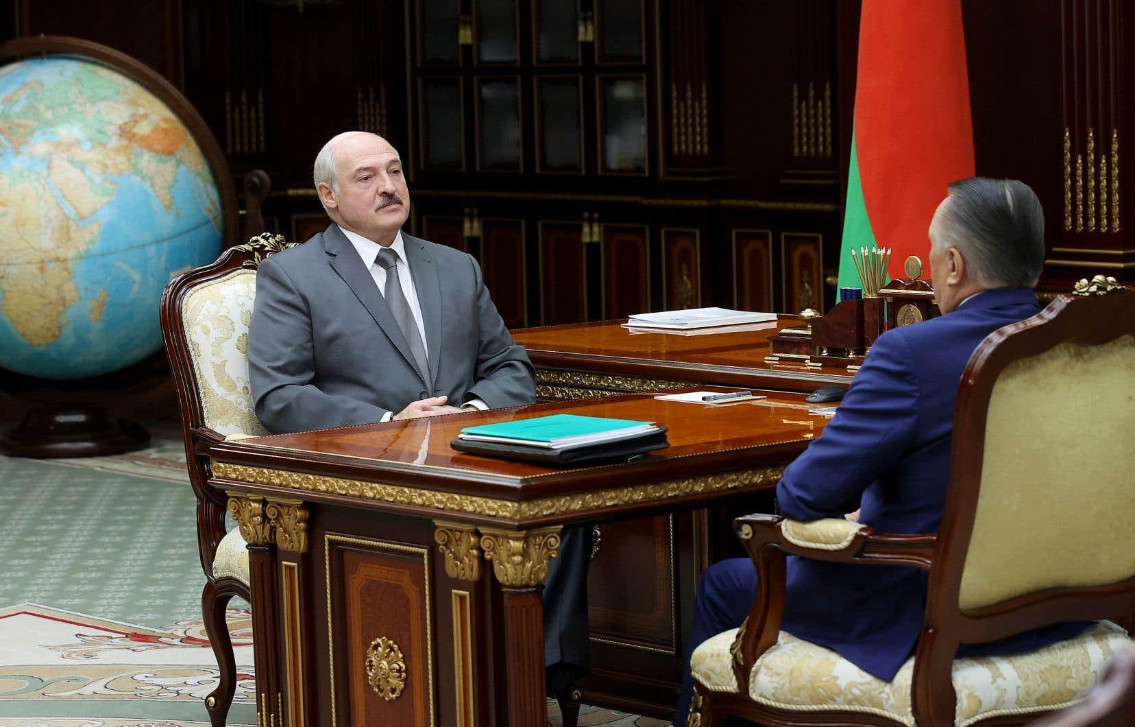 Imperturbable, le président biélorusse Alexandre Loukachenko s'est entretenu lundi avec Valiantsin Sukala, chef de la Cour suprême de la Biélorussie (à droite), à Minsk.