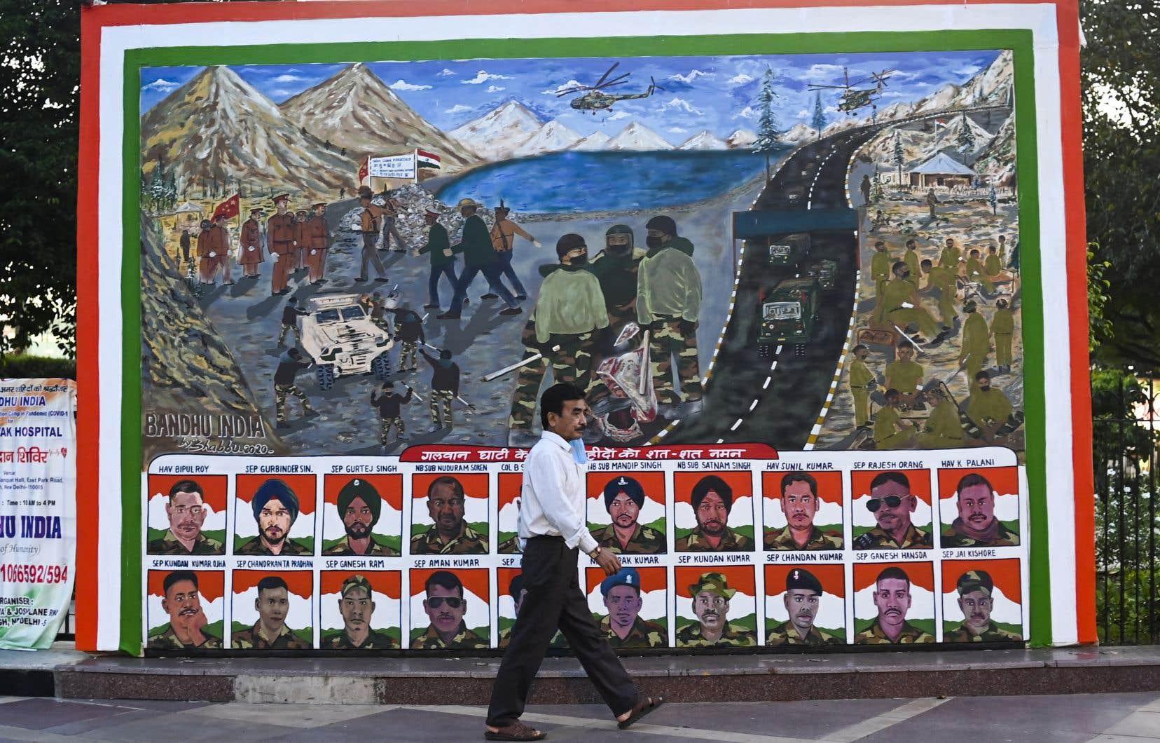 Un homme passe devant une affiche, représentant des portraits de soldats indiens tués dans un combat au corps à corps avec des soldats chinois le 15 juin dernier.