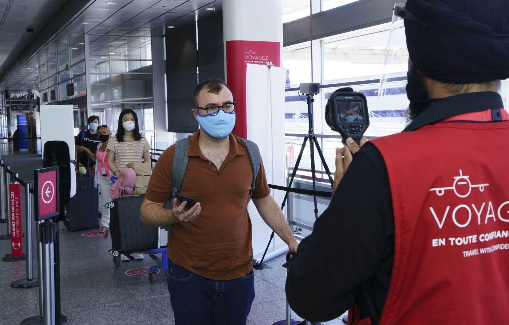 Le personnel prend la température des passagers à leur arrivée à l'aéroport Montréal-Trudeau.