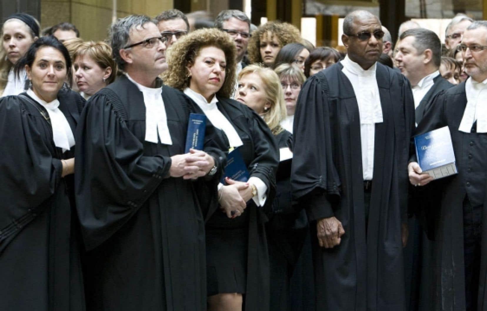 À Montréal, plus de 150 procureurs ont marché silencieusement dans la salle des pas perdus, au palais de justice, pour marquer leur première journée de grève.<br />