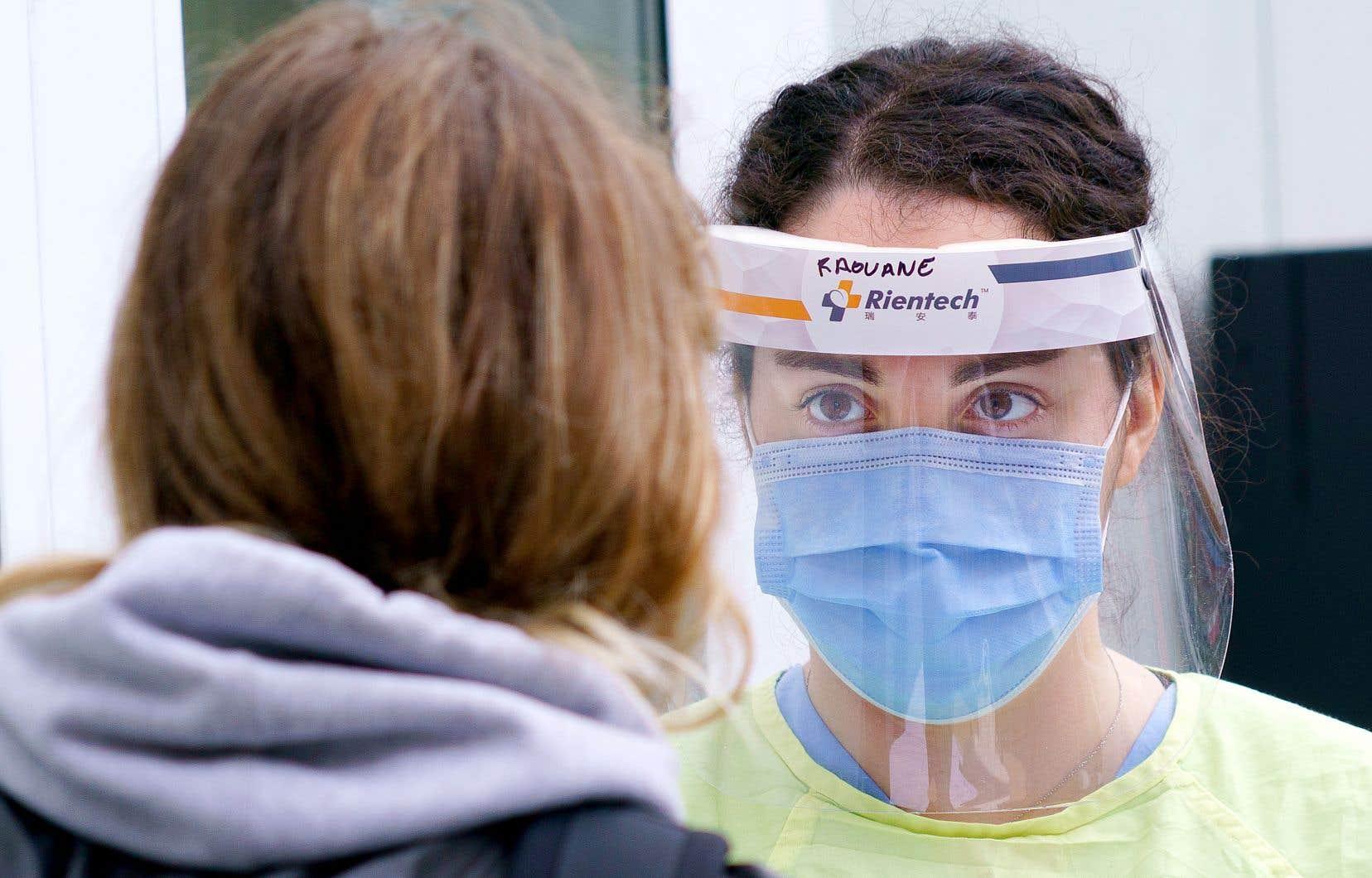 Une infirmière s'apprête à tester une femme dans une clinique mobile de dépistage à Montréal.