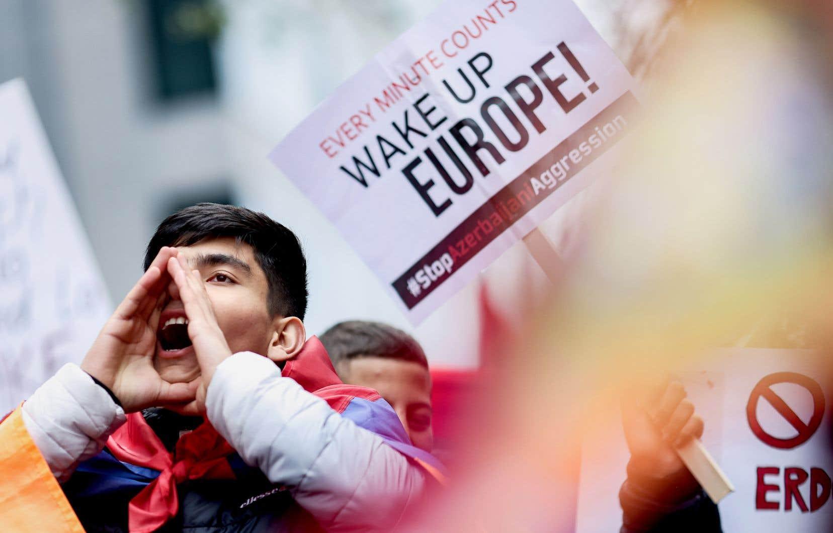 Près du siège de la Commission européenne à Bruxelles, un manifestant lance des slogans réclamant la fin du conflit dans le Haut-Karabakh.