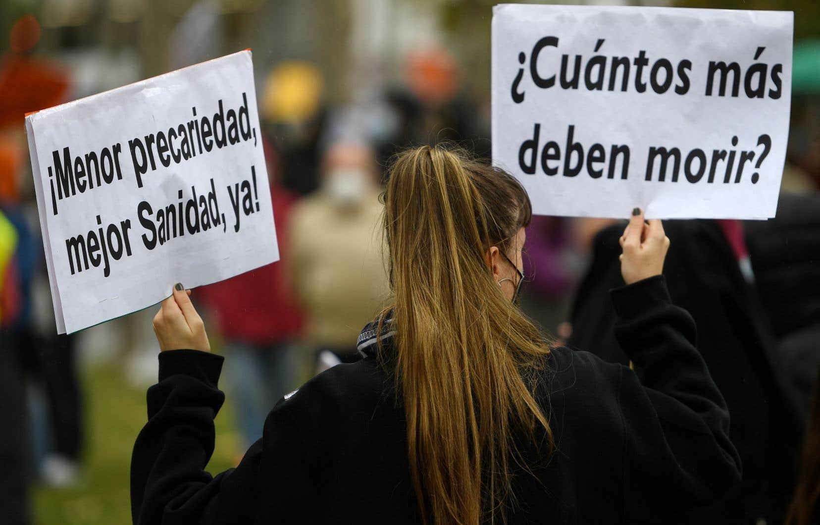 Lors d'une manifestation pour une meilleure gestion de la pandémie et du système de santé, à Madrid, une femme tient une pancarte disant «Combien de personnes de plus doivent mourir?»