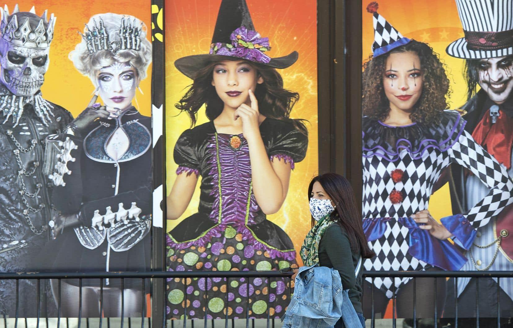 À Montréal, une femme marche devant une boutique qui vend des costumes d'Halloween.