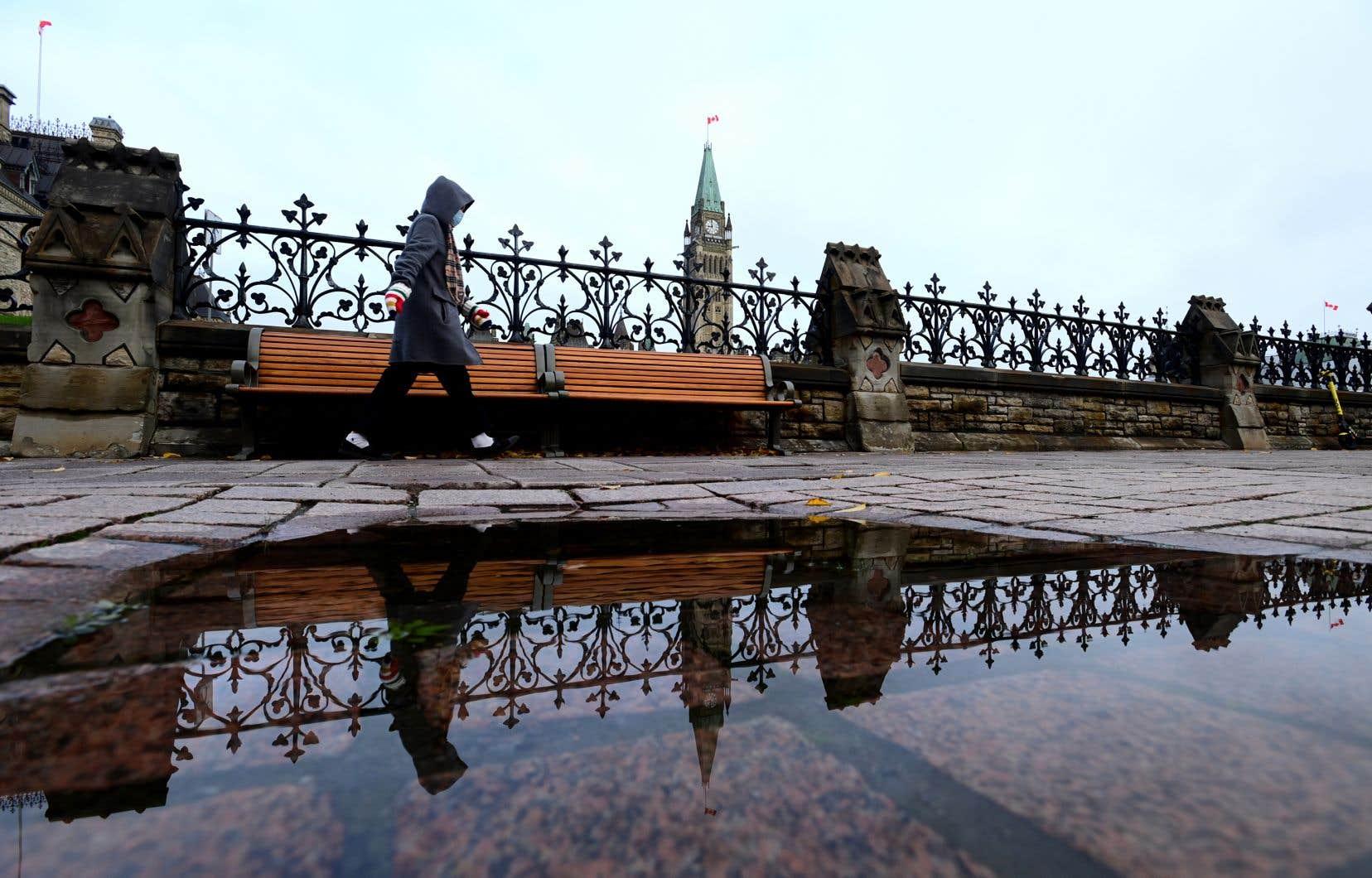 Une personne marchant à proximité des clôtures entourant le terrain du parlement, à Ottawa