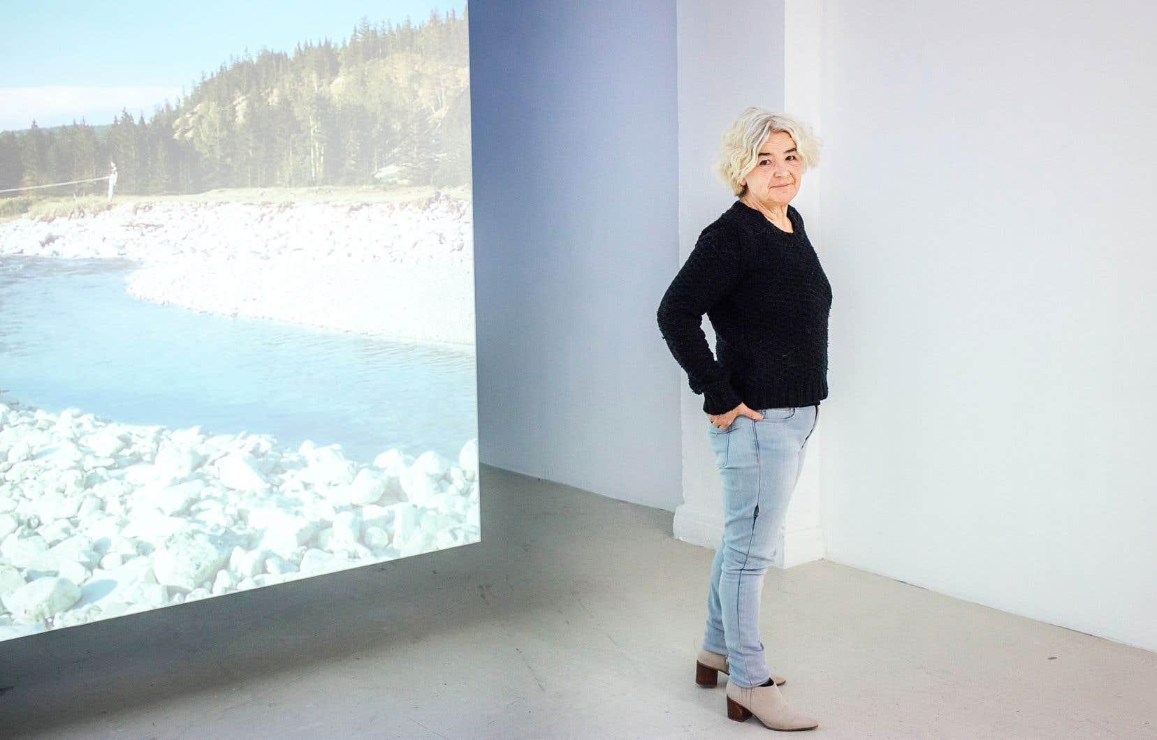 Marthe Carrier, directrice de la galerie B-312, un des quatre centres d'artistes du Belgo, devant une partie d'une œuvre de l'artiste Rachel Echenberg. Le titre de son exposition est Conversations avec ma famille — «Conversations With my Family».