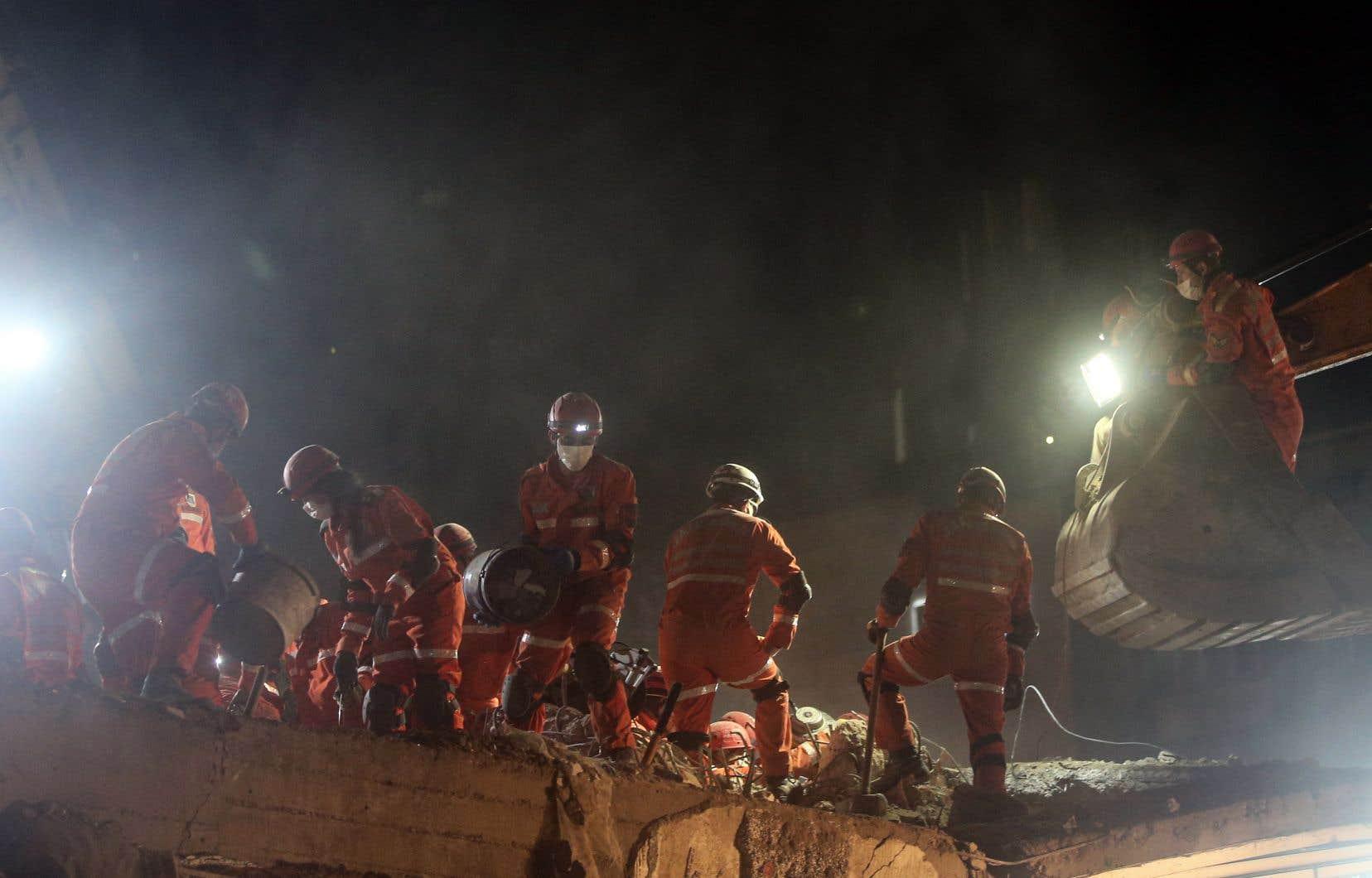 Éclairés par des projecteurs et dans le vacarme des pelleteuses, des équipes de sauveteurs déblayaient un amas de béton et de poutres à Bayrakli, sous le regard inquiet des habitants.