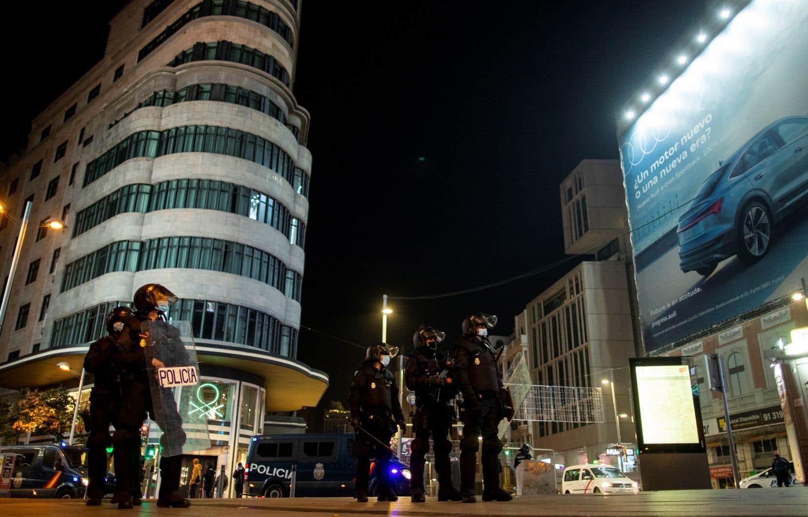 Des policiers anti-émeute à Madrid, en Espagne, où les manifestations contre les restrictions se multiplient.