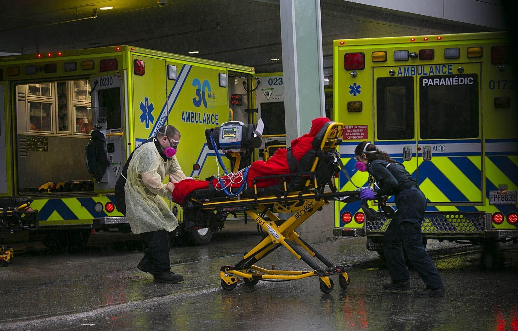 Un patient souffrant de la COVID-19 était transporté par des ambulanciers à l'hôpital Jean-Talon de Montréal, au printemps.