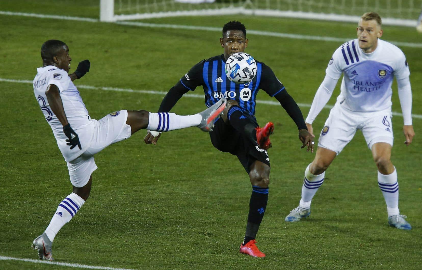 Sebastian Mendez, de l'Orlando City SC, et Romell Quioto, de l'Impact de Montréal, ont bataillé ferme pour le contrôle du ballon lors du match qui a opposé les deux équipes, dimanche.