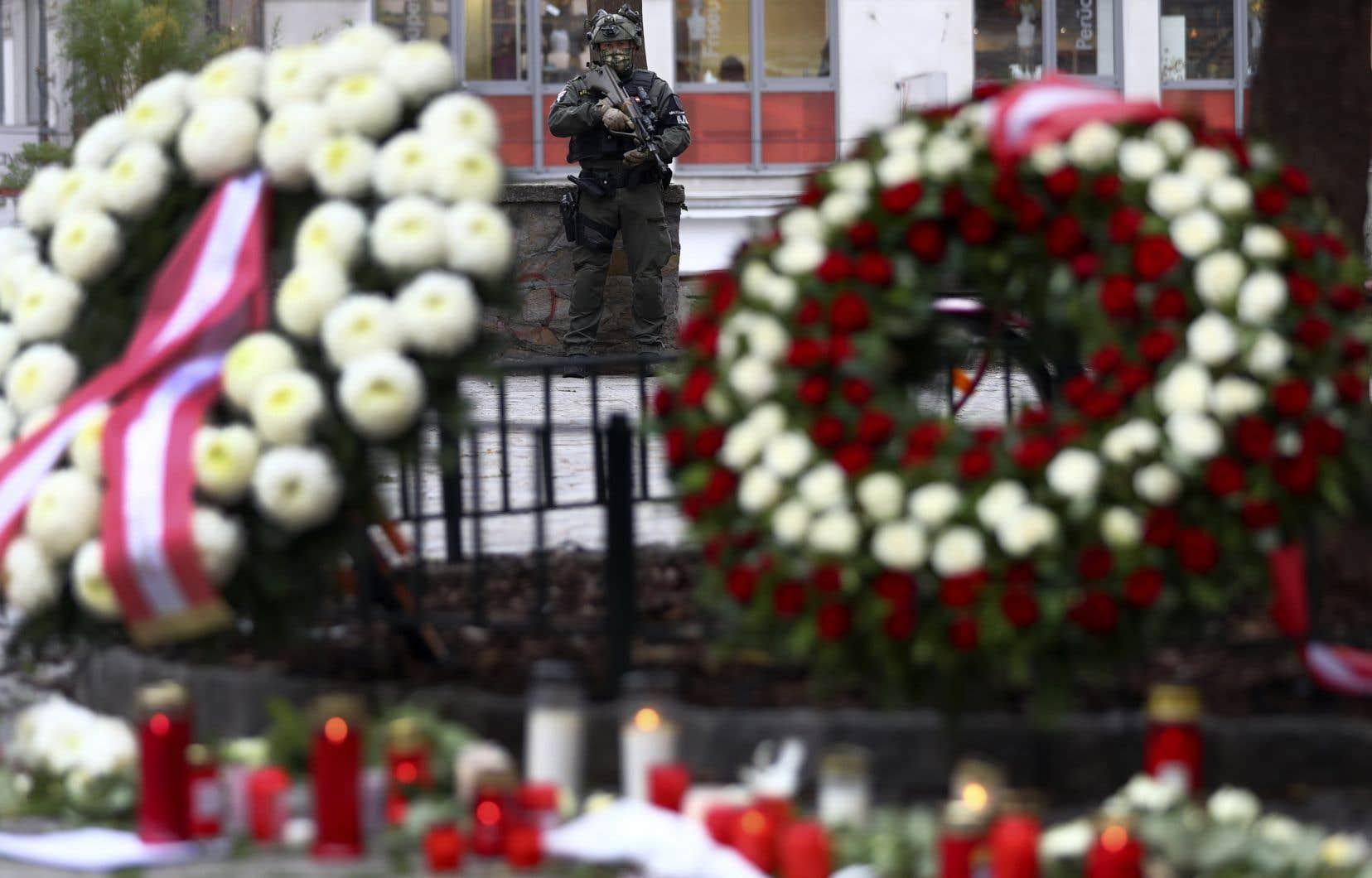 Un membre des forces de l'ordre surveille le site de l'attaque, au centre-ville de Vienne, où des chandelles et des fleurs ont été déposées en mémoire des victimes.