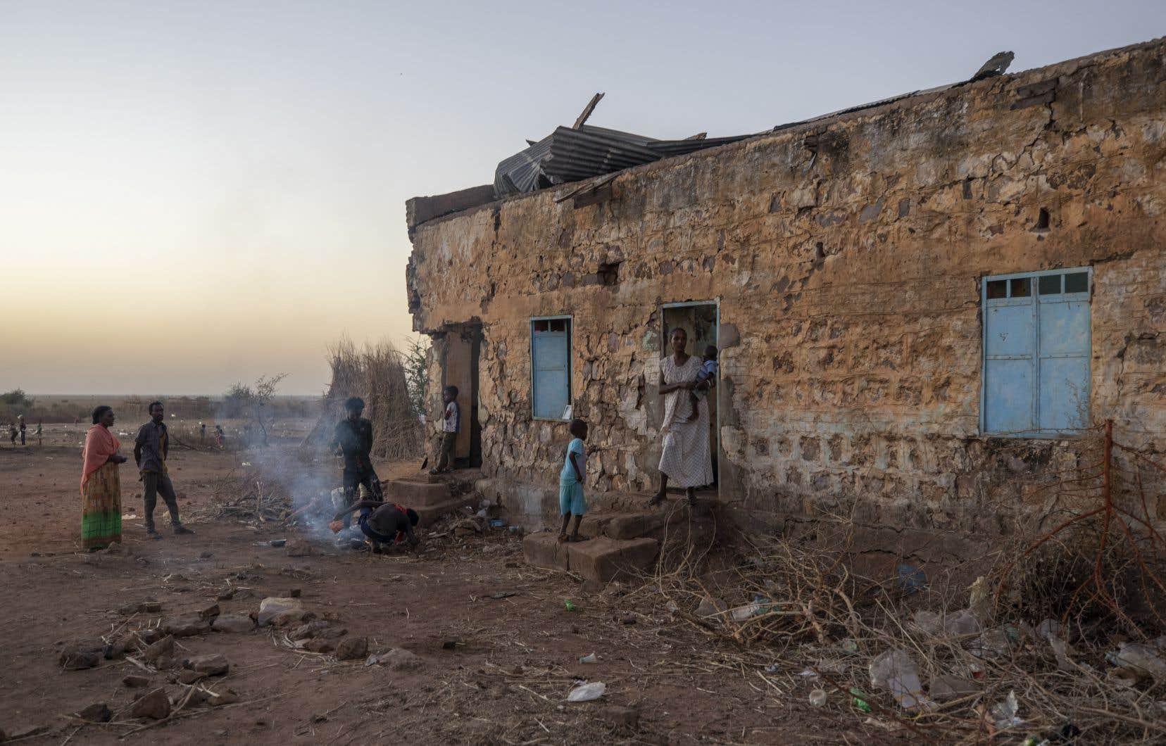Des Éthiopiens qui ont fui le Tigré préparaient un feu, lundi, près d'un camp, de réfugiés de l'est du Soudan .