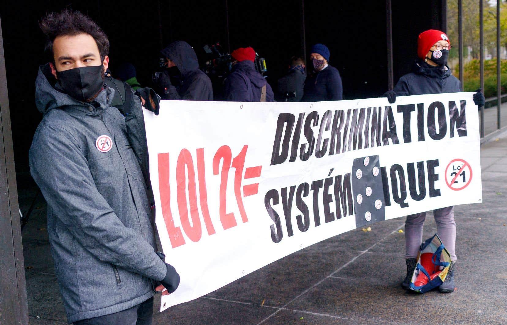 Ceux qui contestent la loi 21 estiment qu'elle est notamment discriminatoire envers les minorités religieuses, dont les femmes musulmanes, qui seraient particulièrement visées par la loi, disent-ils. Sur la photo, des manifestants devant la palais de justice de Montréal, en novembre.
