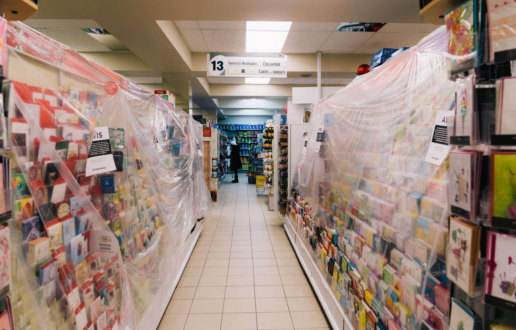 Dans ce Jean-Coutu de Montréal, les rayons où sont stockés les produits jugés non essentiels sont recouverts d'une pellicule de plastique pour empêcher les clients d'y toucher.