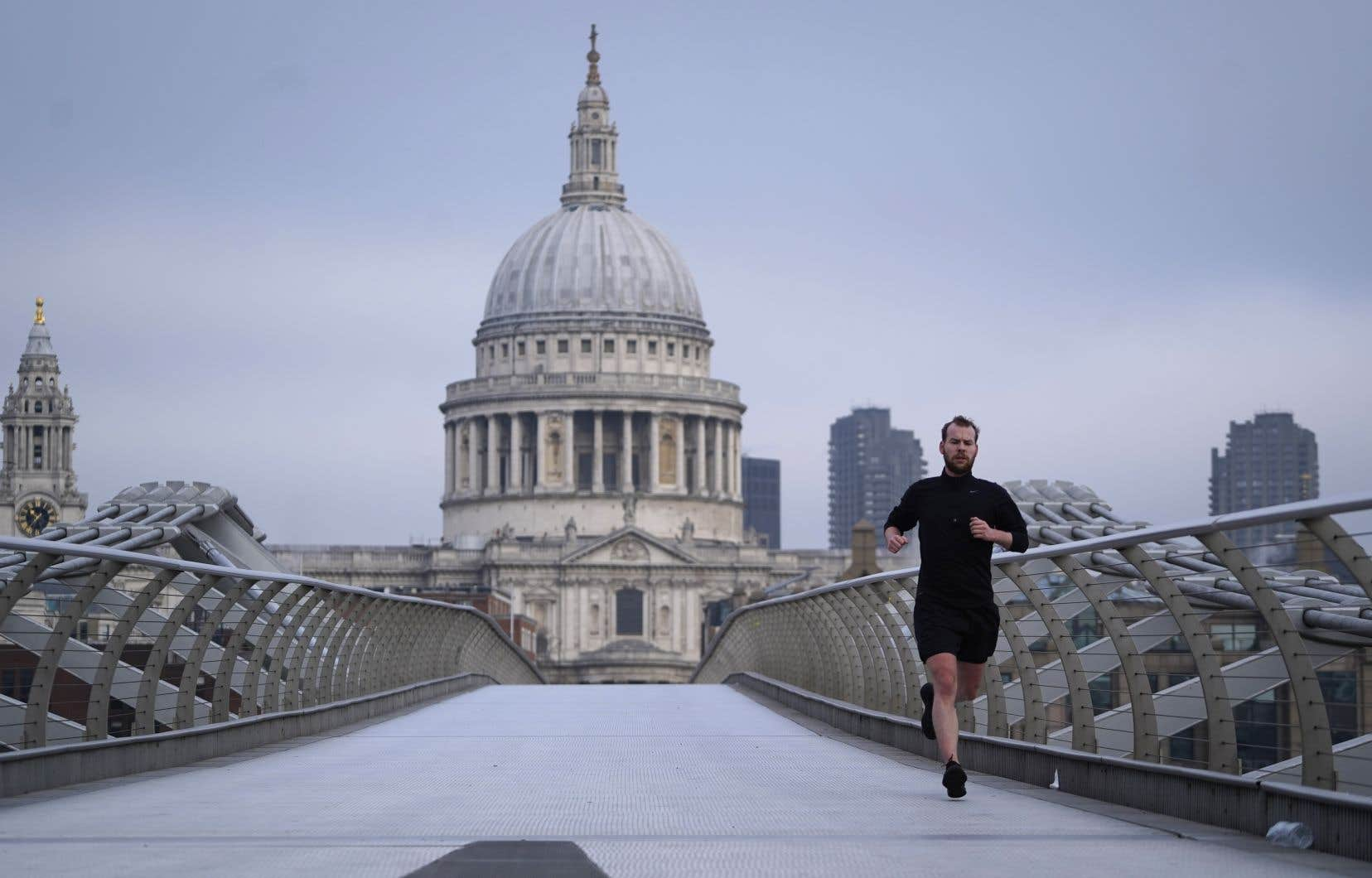 Un coureur profitait des lueurs de l'aube et des rues désertes pour arpenter Londres, jeudi matin.