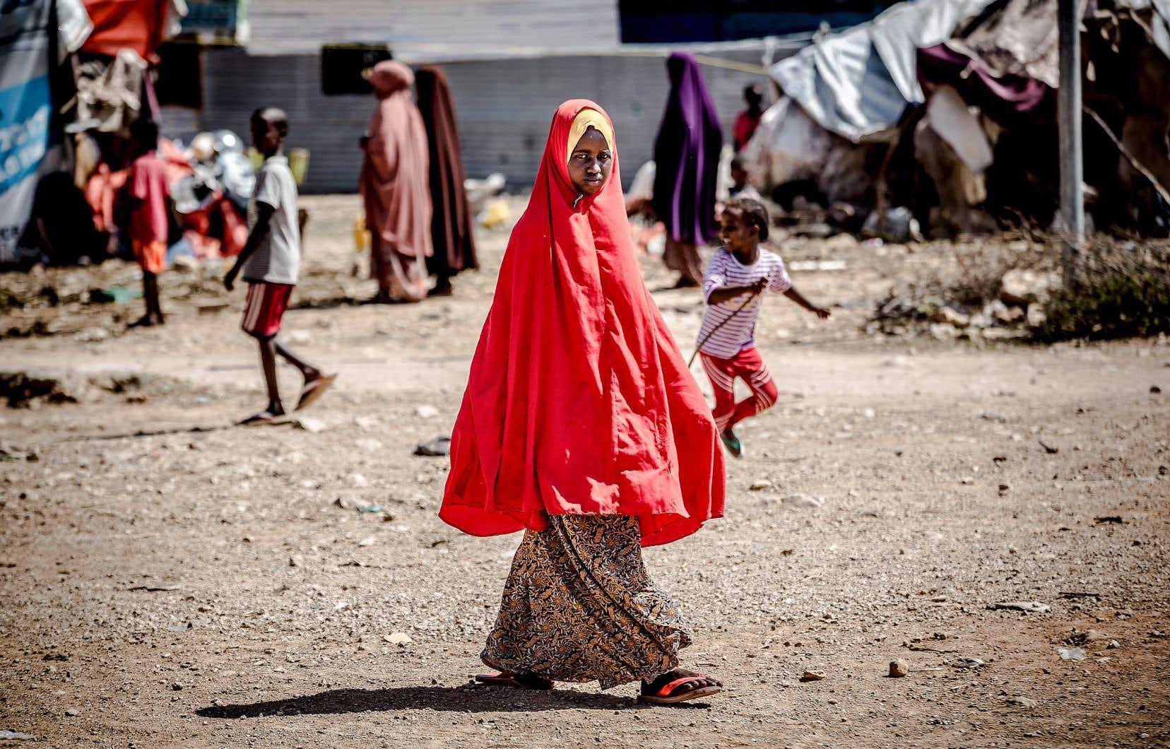 Une jeune femme se promenant dans un camp de personnes déplacées à Beledweyne, en Somalie, après que des pluies massives — phénomène de plus en plus fréquent avec le réchauffement climatique — eurent inondé de grandes aires du pays en décembre 2019.